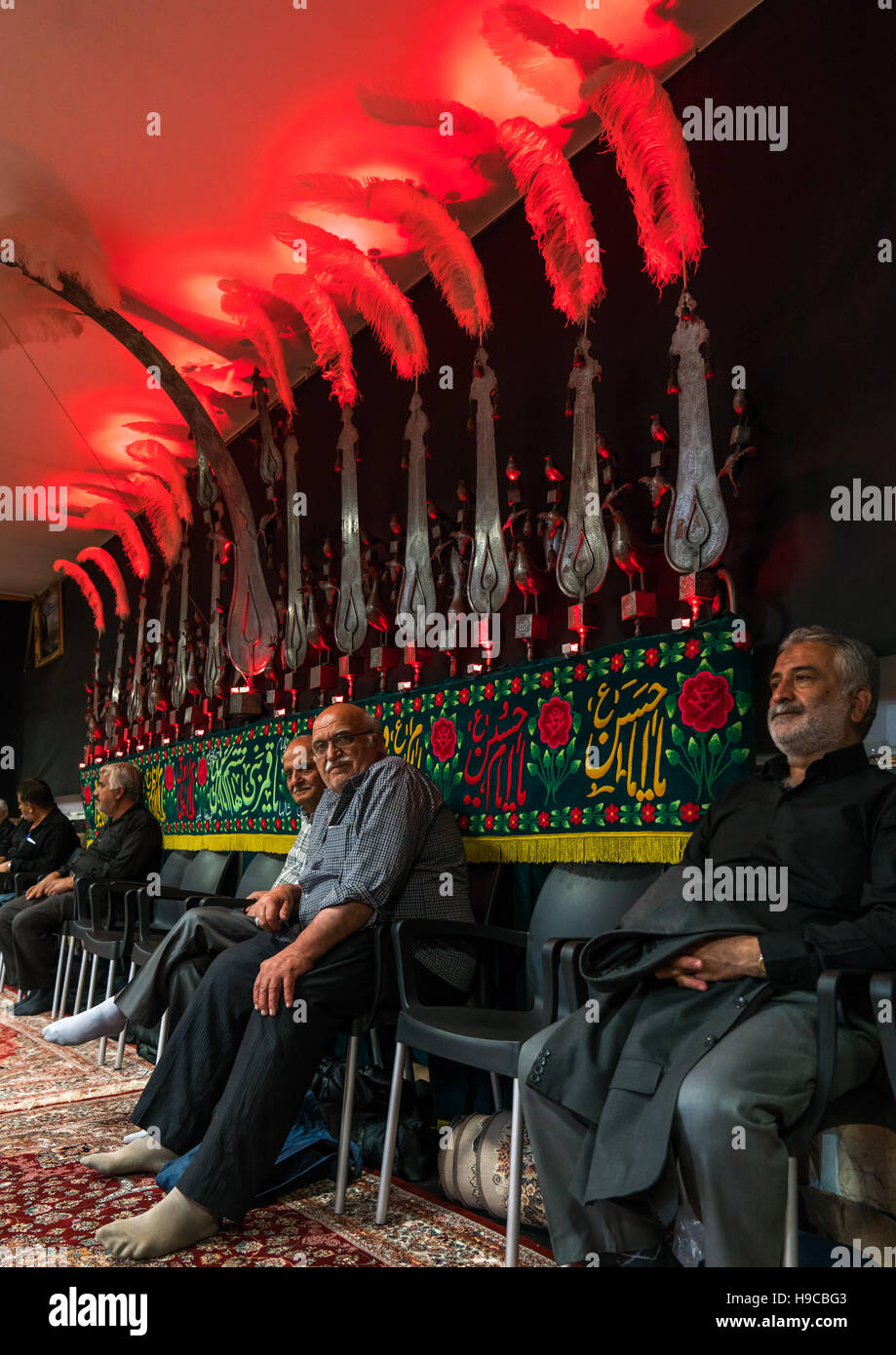 Shiite men standing under an alam in a hosseinieh decorated for muharram, Isfahan province, Kashan, Iran - Stock Image