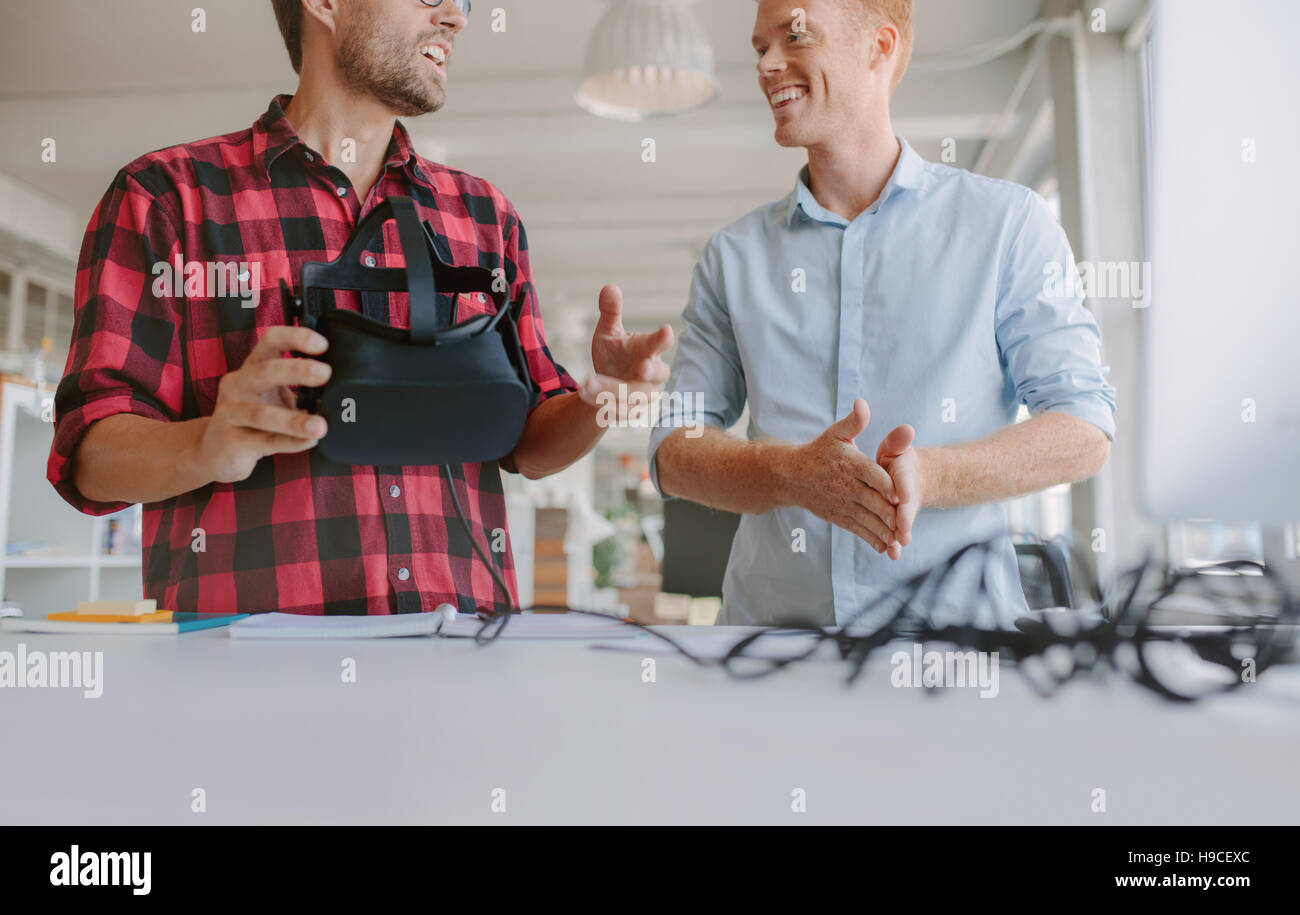 Cropped shot of two young men testing virtual reality headset. Business men discussing and testing VR glasses. - Stock Image