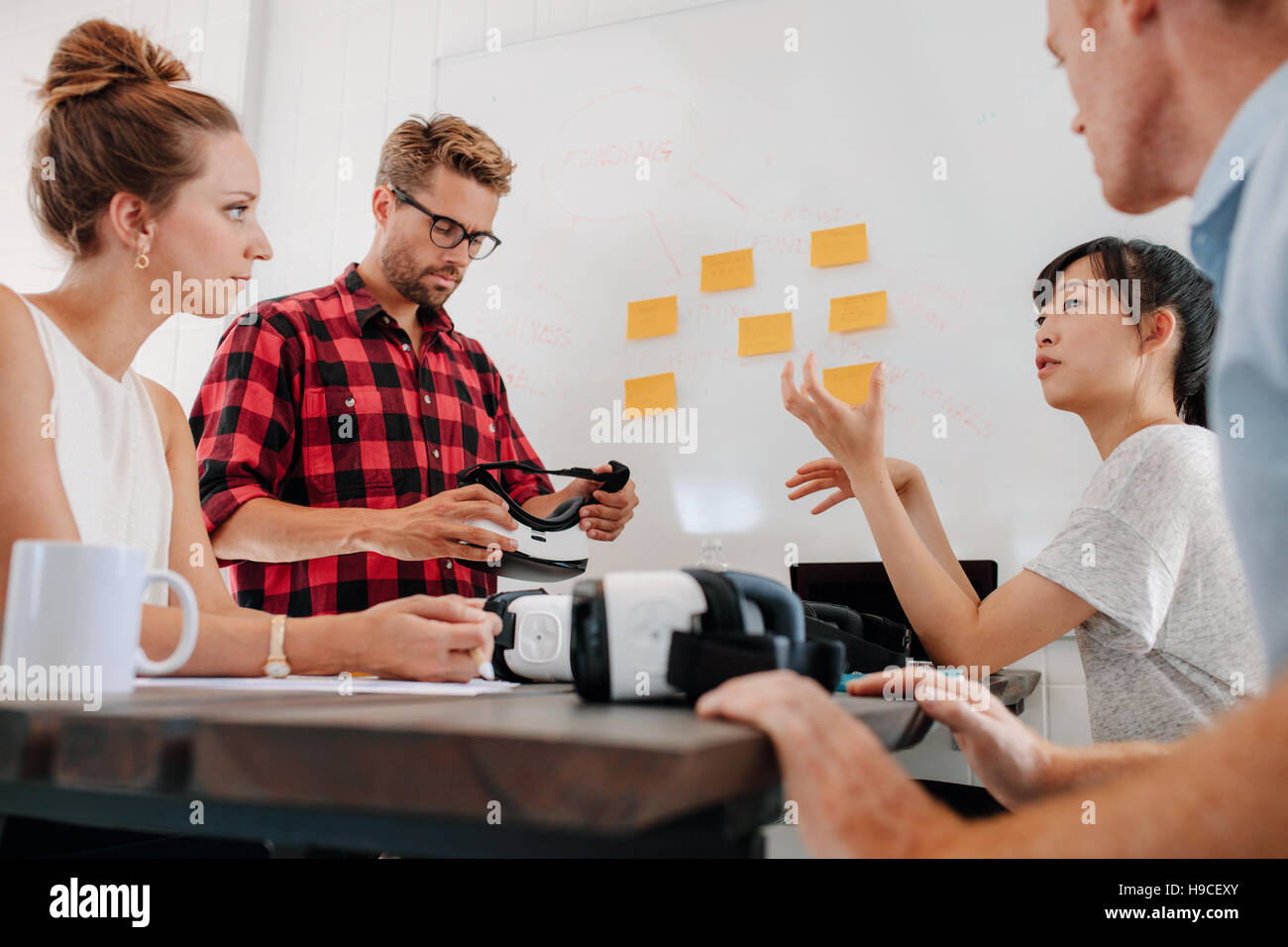 Group of young people meeting in conference room with augmented reality devices on table. Diverse business team - Stock Image