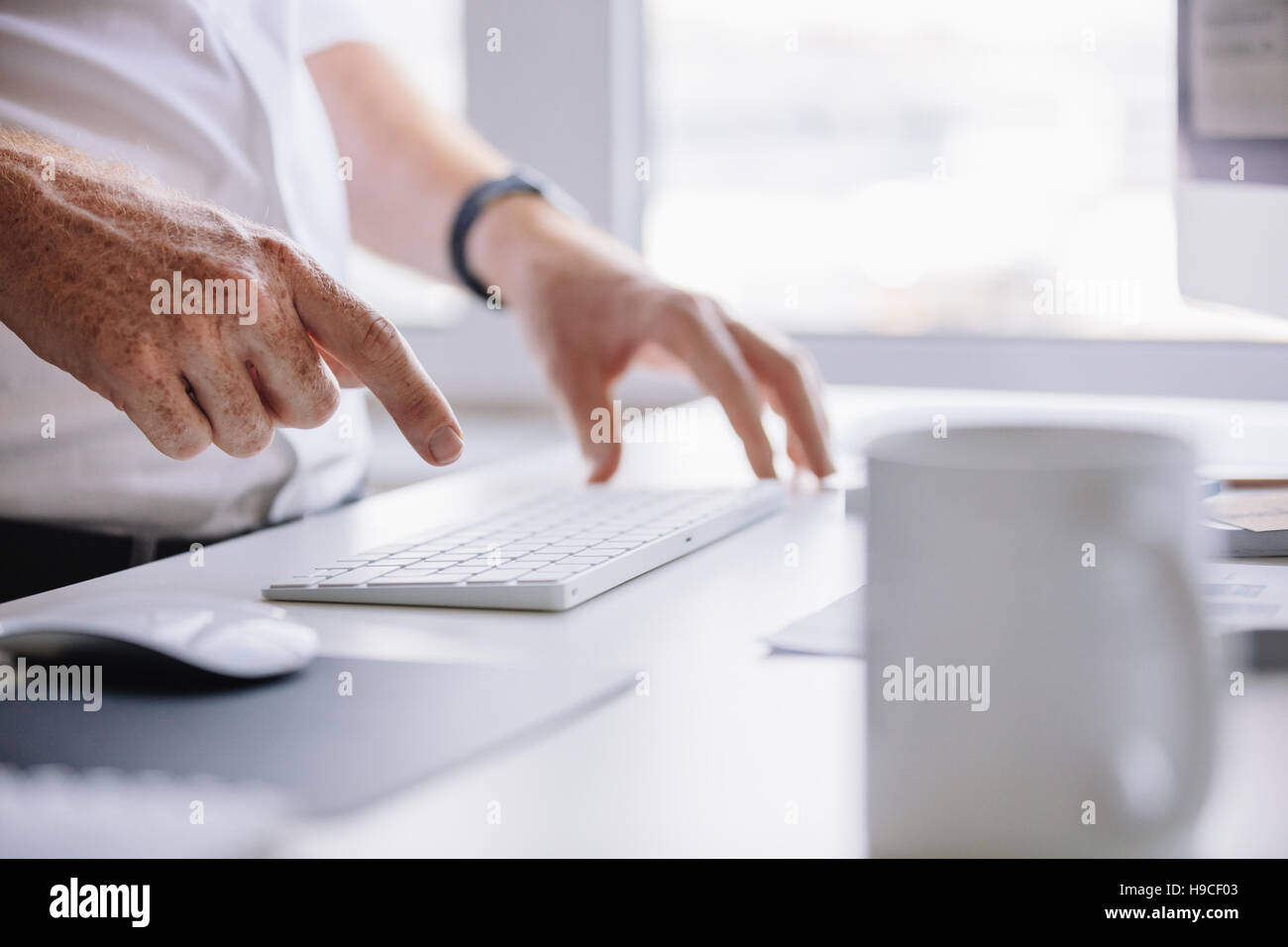 Close up shot of young man hands typing on wireless keyboard on desk in office. - Stock Image