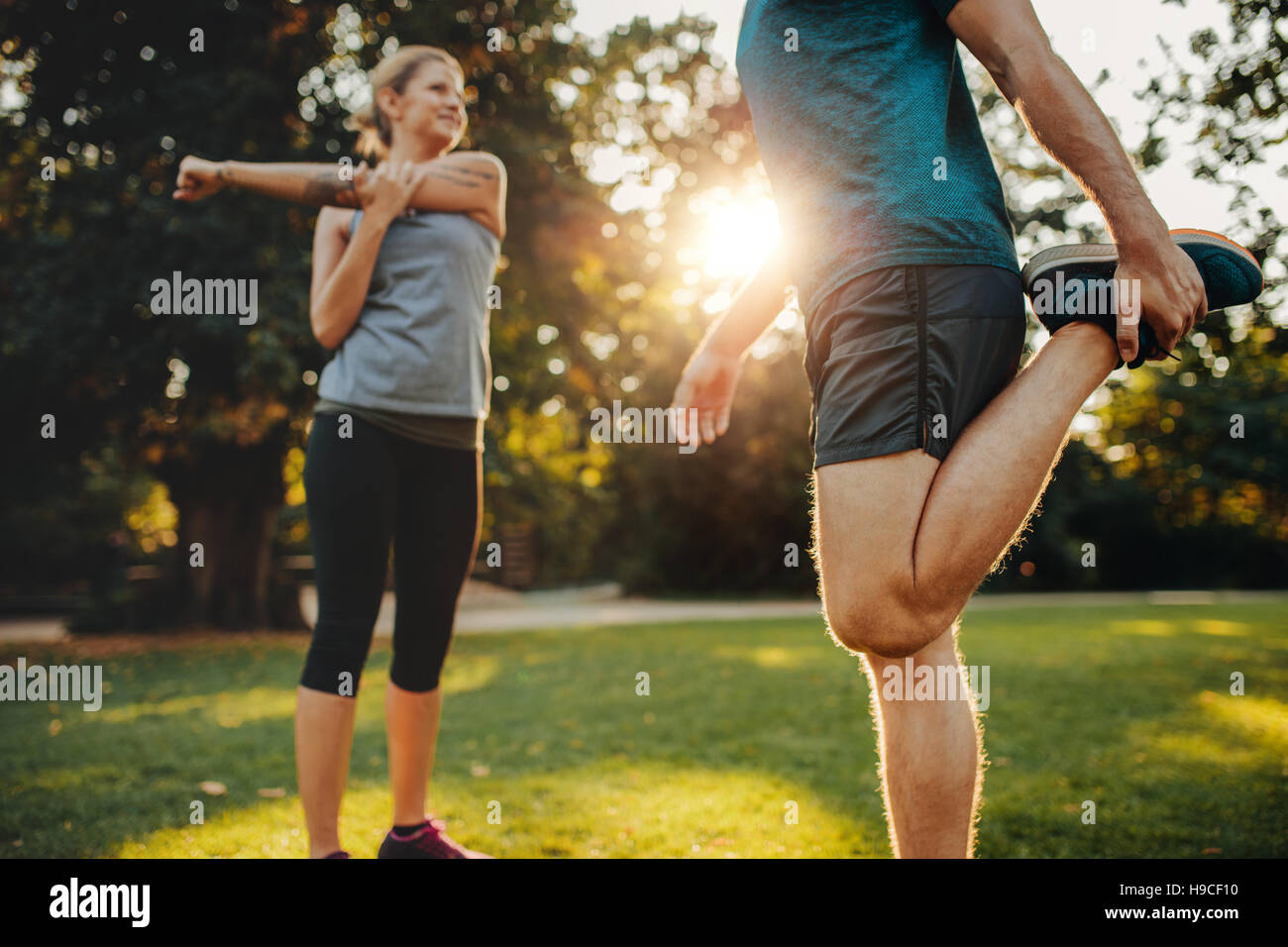 Shot of young man and woman stretching in the park. Young couple warming up in morning. - Stock Image