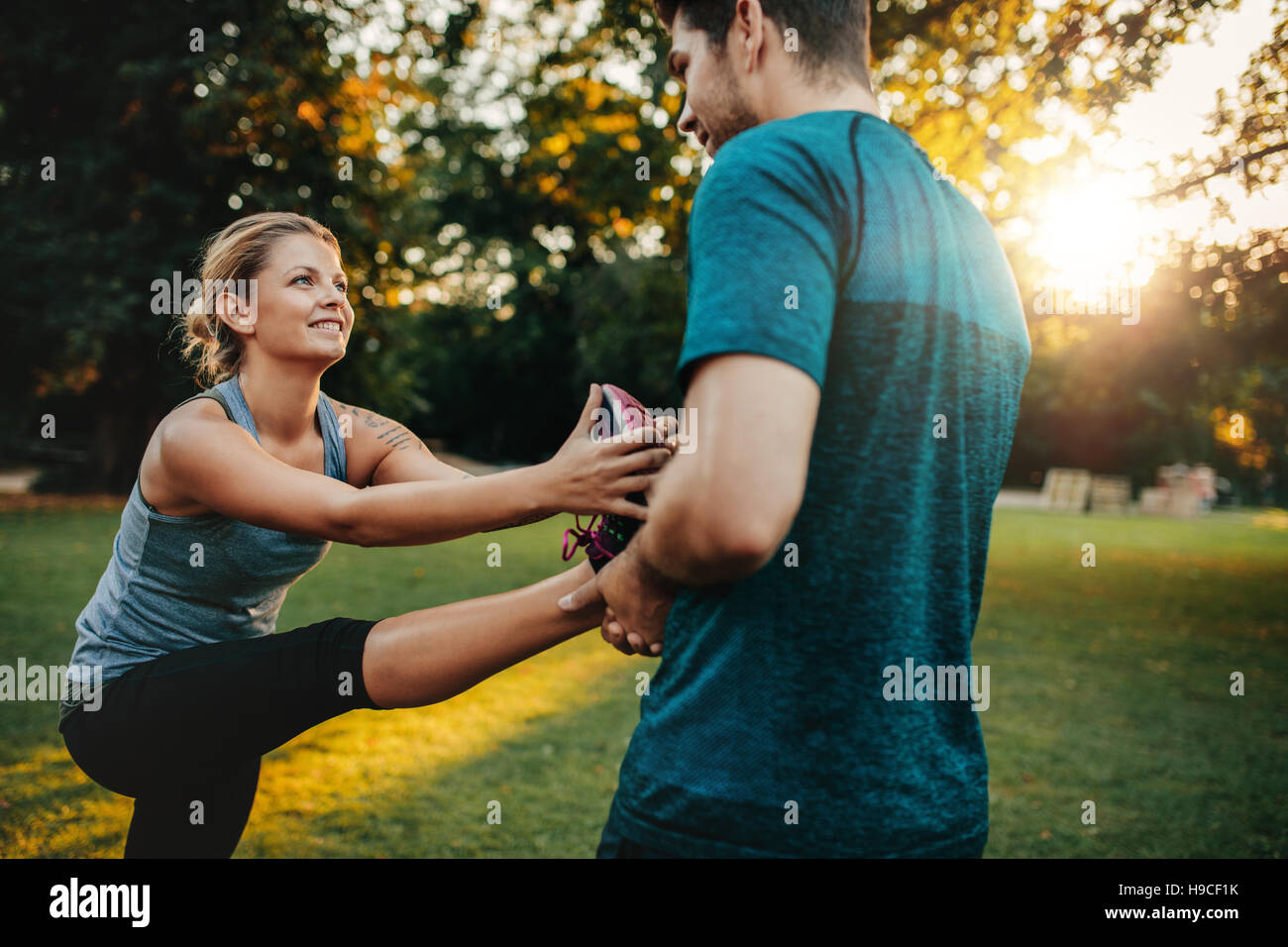 Male physical trainer assisting woman with leg exercise. Young woman being assisted by personal trainer in stretching - Stock Image