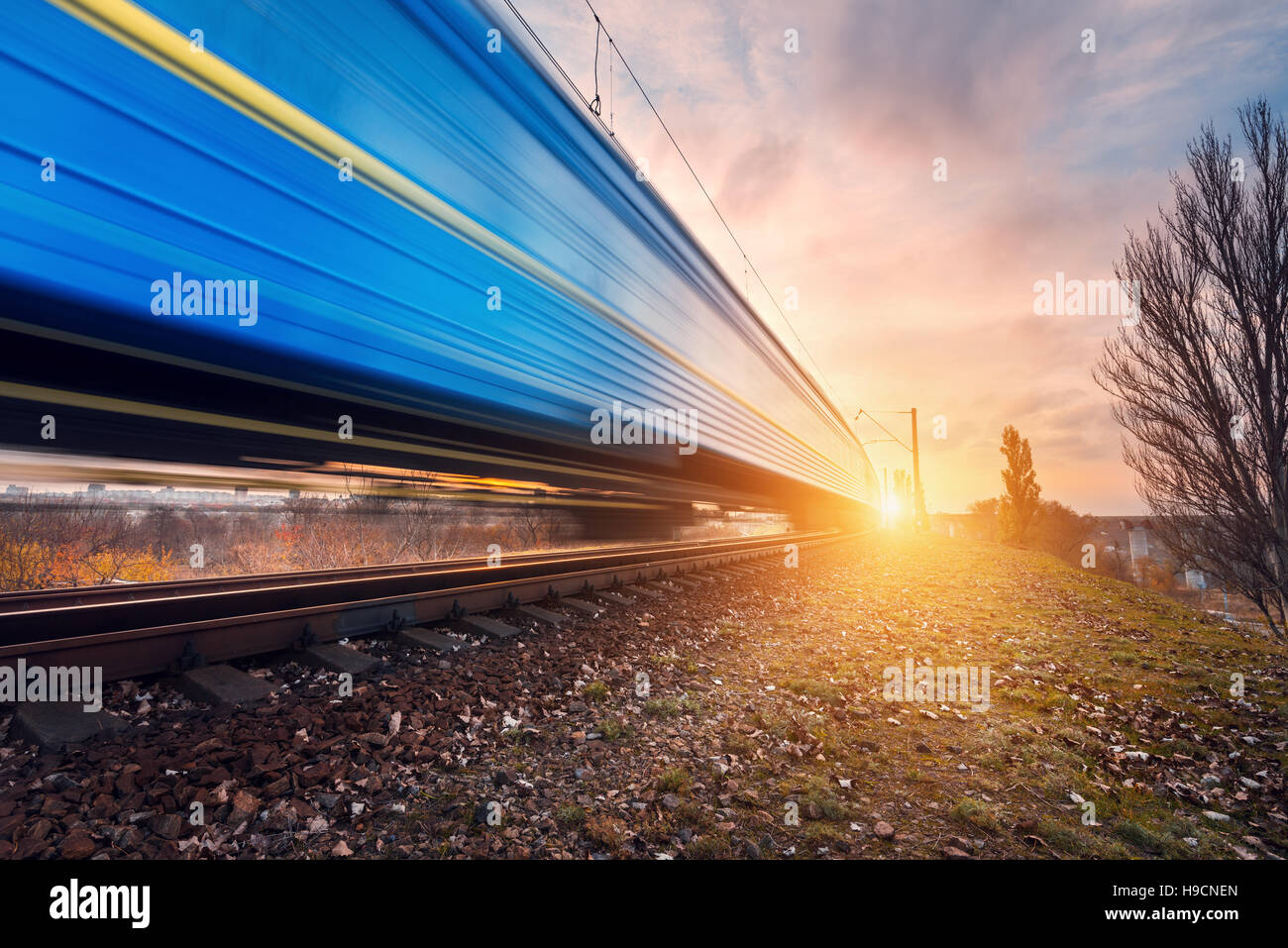 High speed blue passenger train on railroad track in motion at sunset. Blurred commuter train. Railway station. - Stock Image