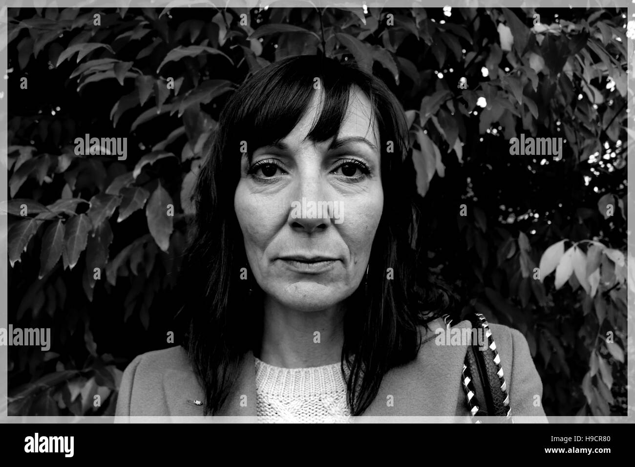 Close up Black and White Portrait of Woman with a sad and moody expression in front of leaves - Stock Image