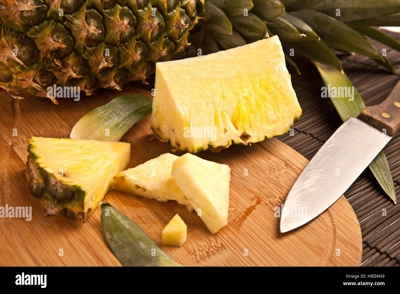 Fresh slice pineapple on a wooden plank - Stock Image