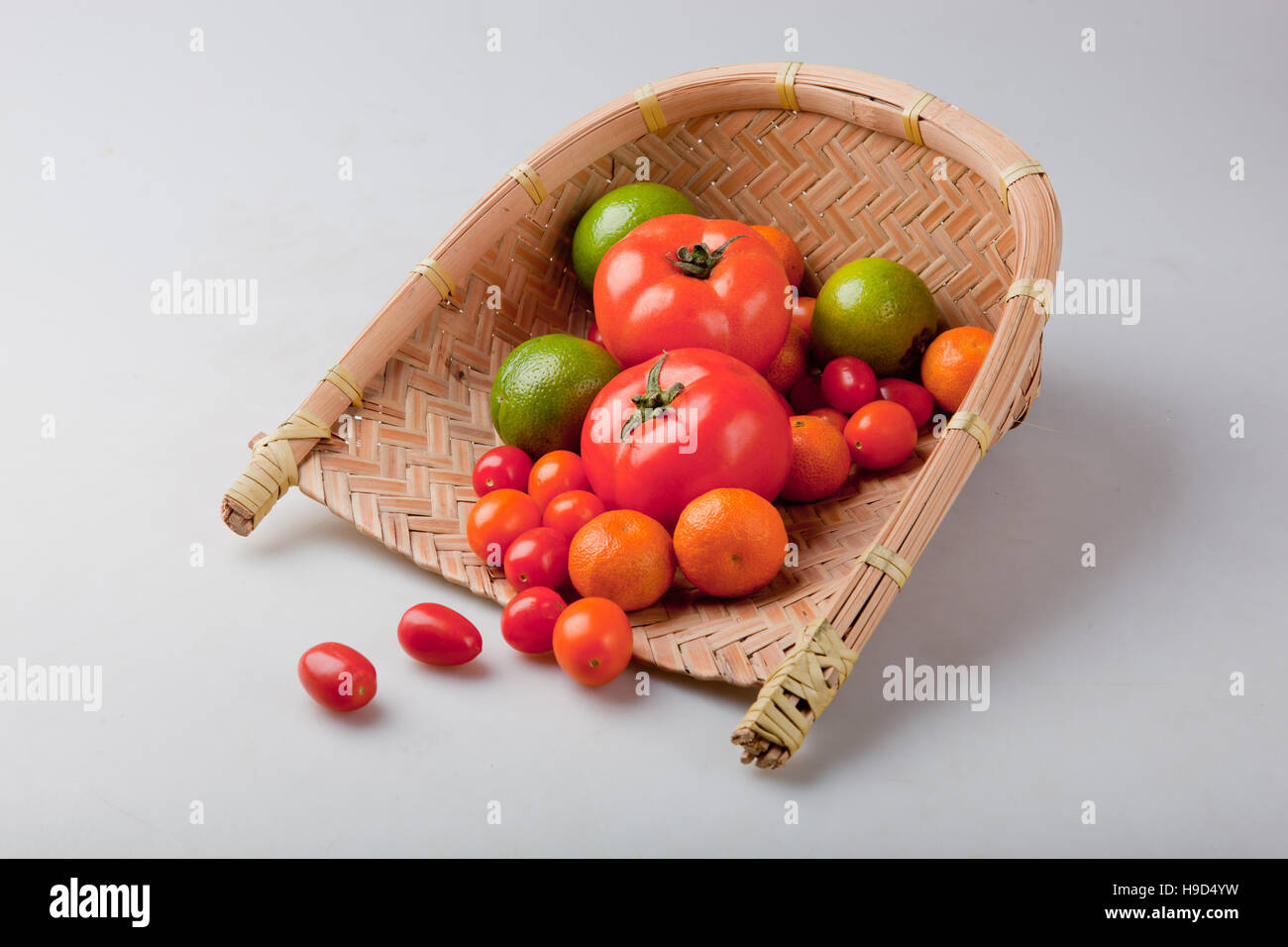 Assortment of exotic fruits in basket, isolated on white - Stock Image