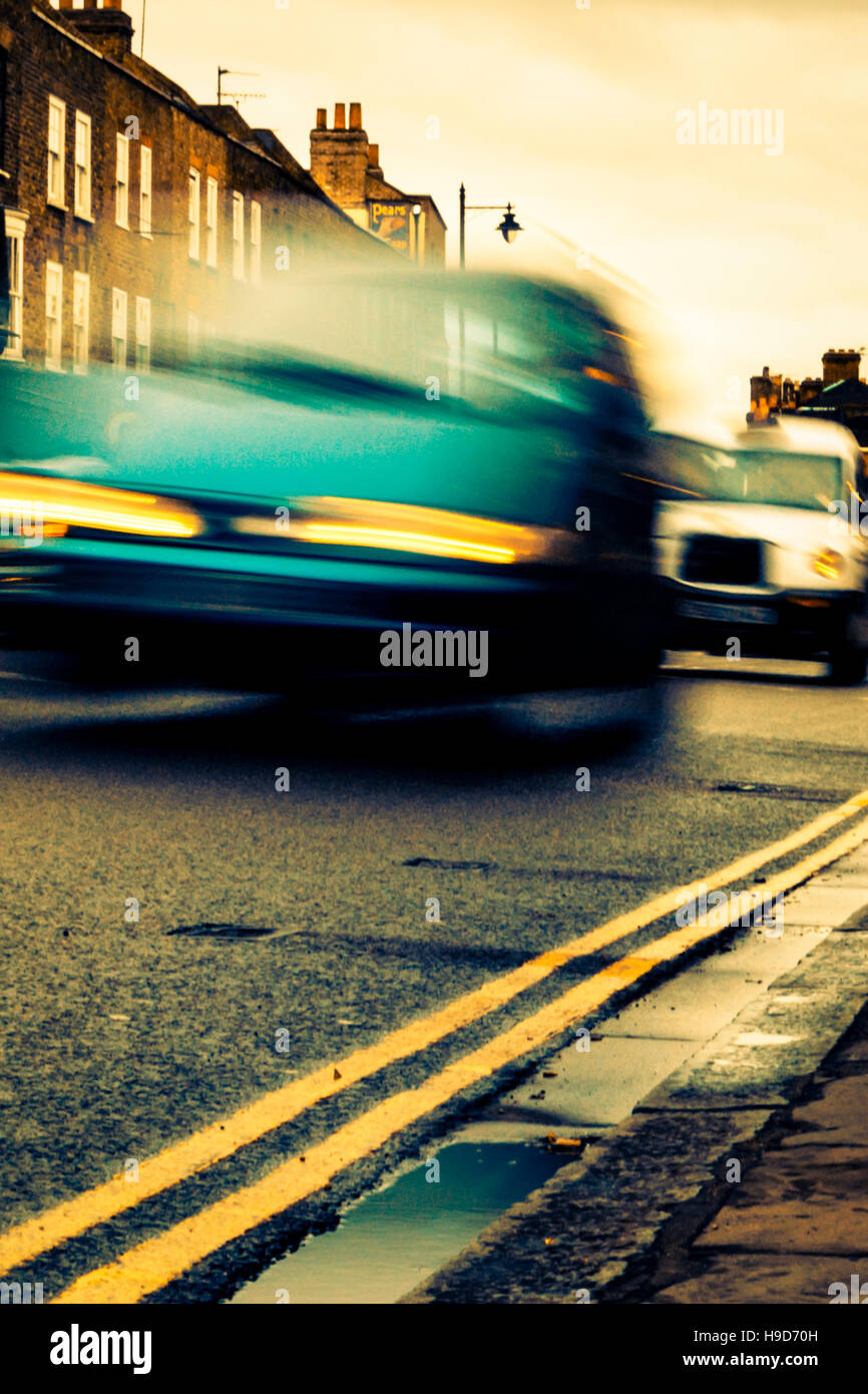 Atmospheric book-cover style low-angle image of motion-blurred cars at night Stock Photo