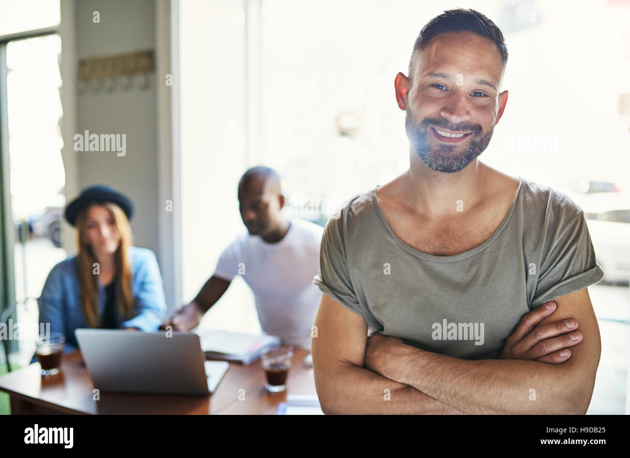 Casual looking male posing with hands crossed on blurred background of co-workers sitting at table in office. - Stock Image