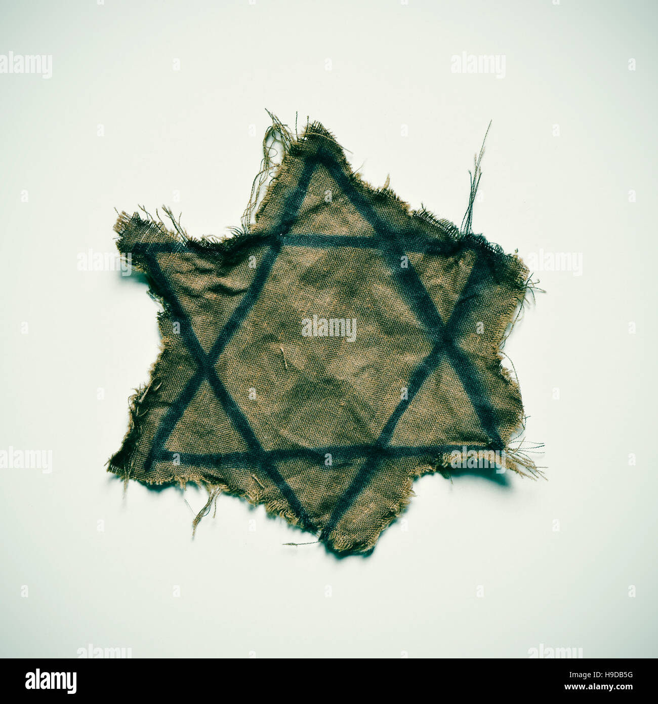 closeup of a ragged Jewish badge on an off-white background - Stock Image