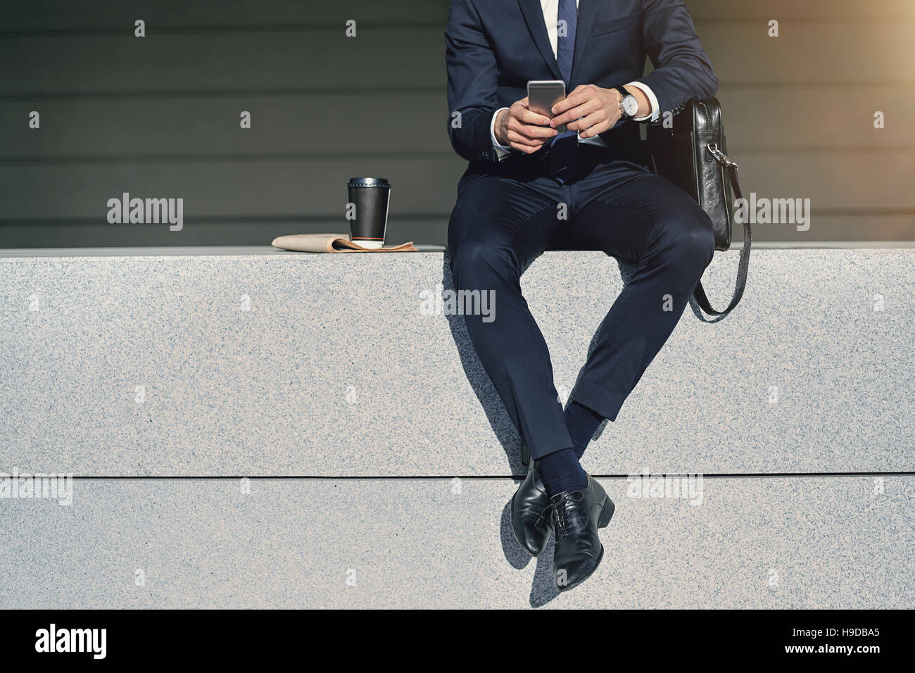 Crossed legs of businessman sitting with cellphone. Horizontal outdoors shot - Stock Image