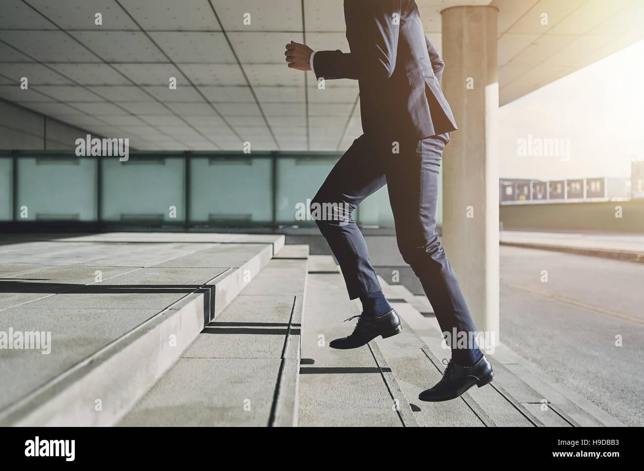 Businessman running fast upstairs. Horizontal outdoors shot. Stock Photo