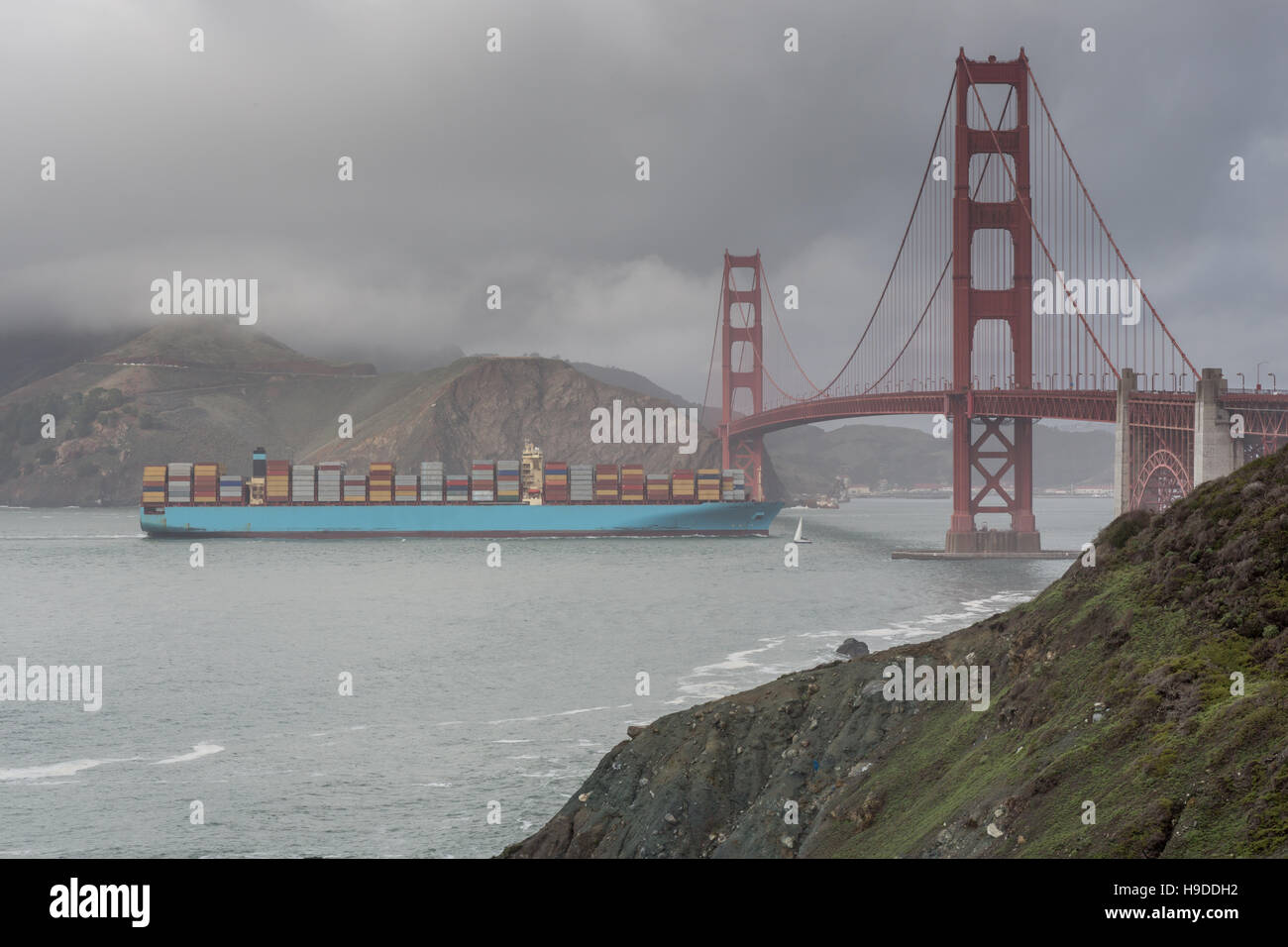 Freight ship crossing the Golden Gate Bridge during storm. - Stock Image