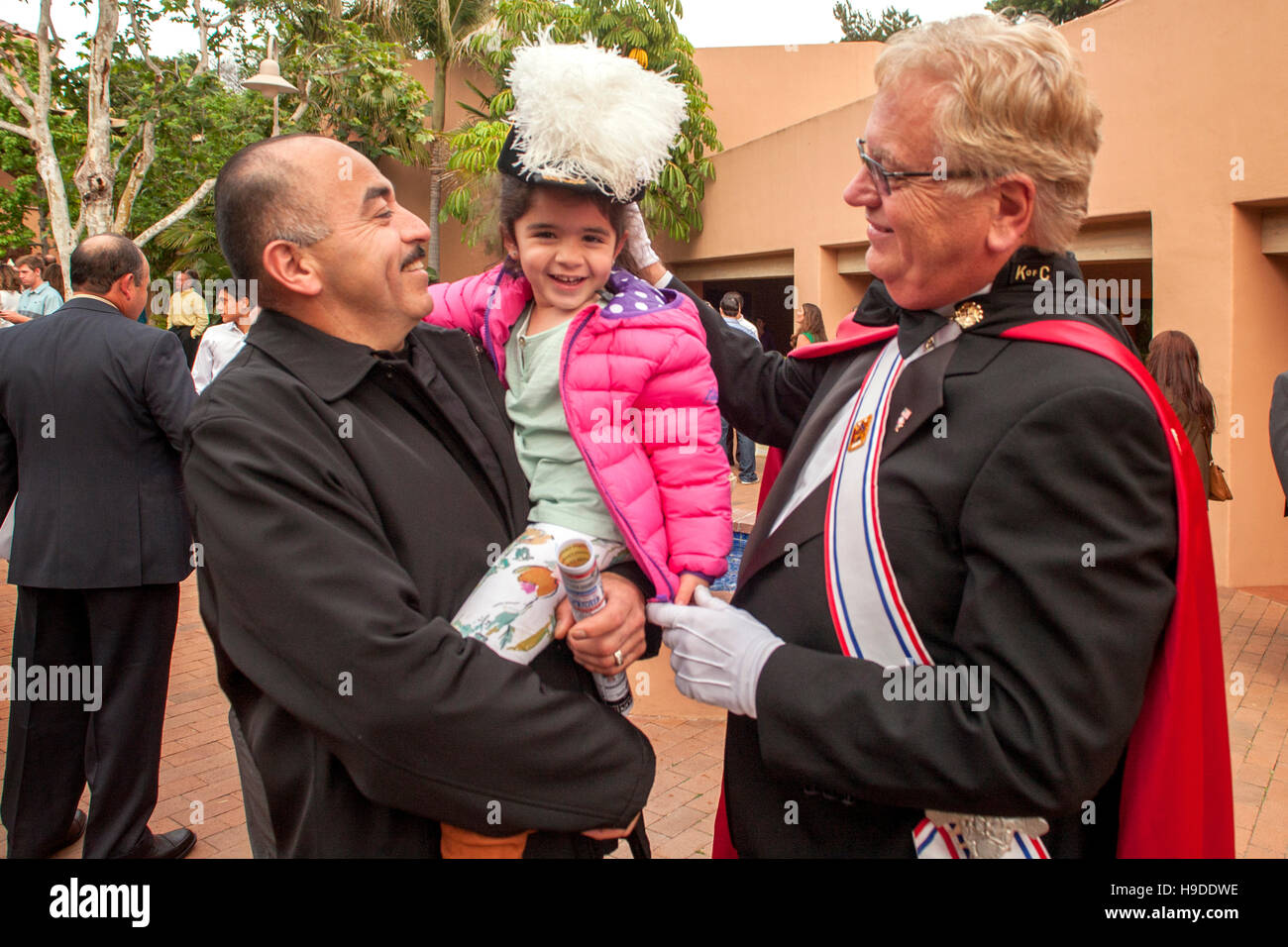 A little girl in her father's arms tries on the plumed hat of an elaborately costumed member of the Knights of Columbus Stock Photo