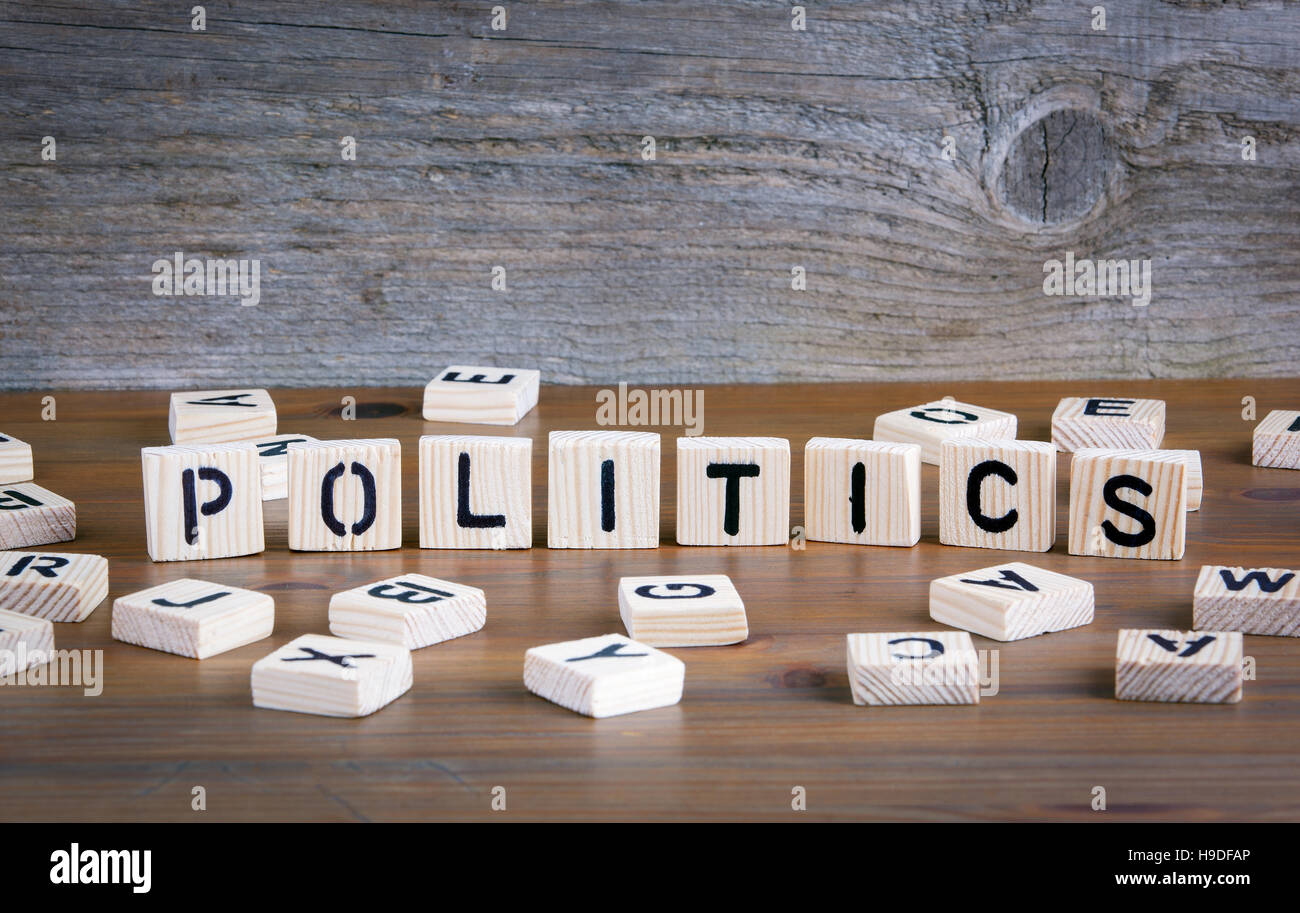 Politics from wooden letterson on wooden background - Stock Image