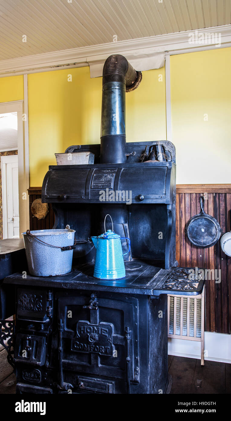 Historic home interior with a coal stove or wood burning stove with a porcelain coffee pot and bucket, Colorado, - Stock Image