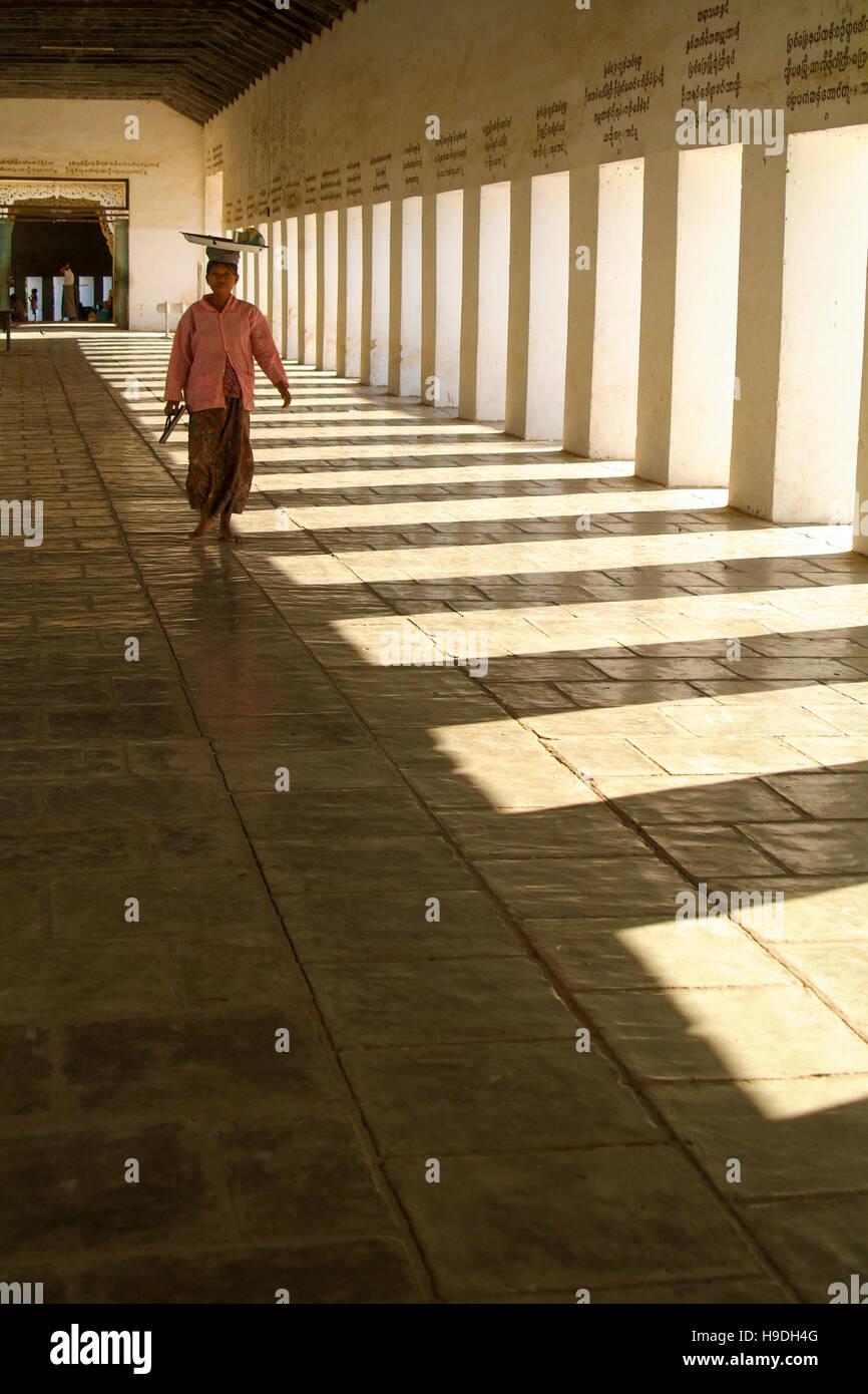 A woman in the walkway to the Shwezigon Pagoda in the town of Nyaung-U near Bagan in Myanmar Stock Photo