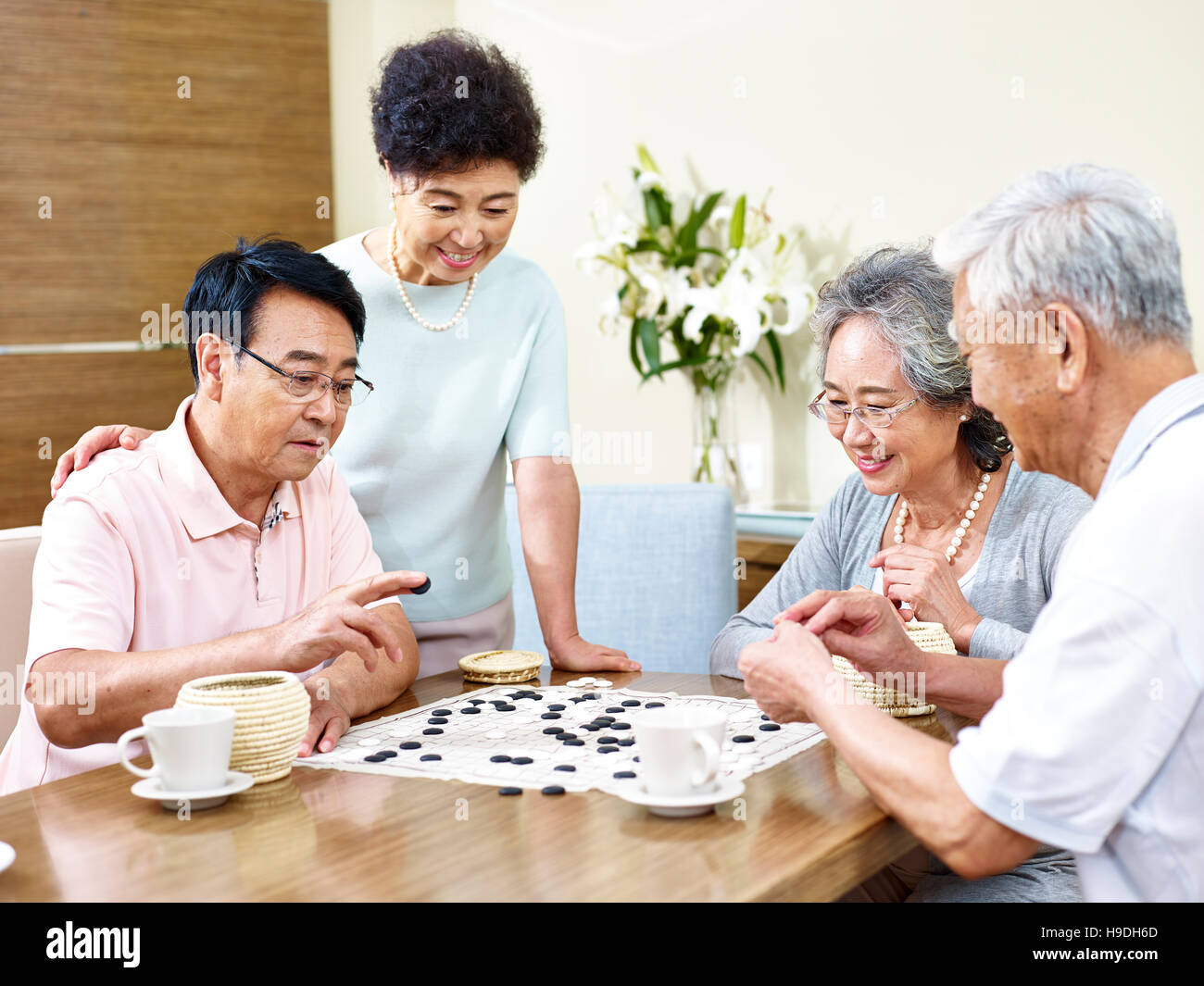 two senior men playing Weiqi (or game of go) at home with their wives watching - Stock Image