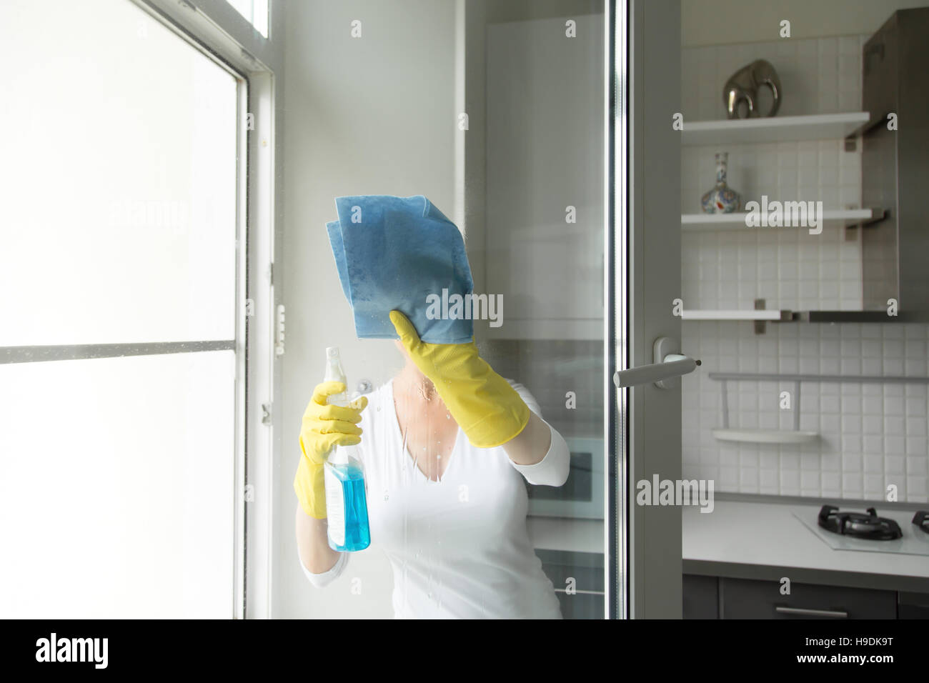 Young woman washing the windows - Stock Image