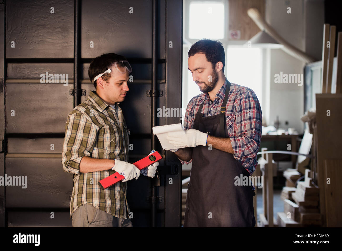Happy male carpenter showing something to coworker ruler and notebook in workshop - Stock Image