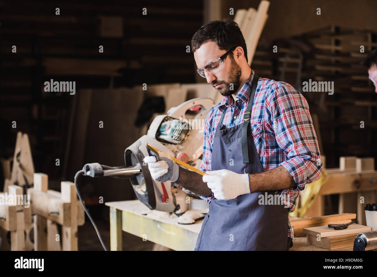 Handsome carpenter in protective glasses standing near his wooden object in the workshop - Stock Image