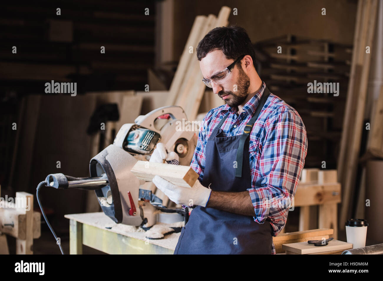 Handsome carpenter in protective glasses standing near his wooden object in the workshop Stock Photo
