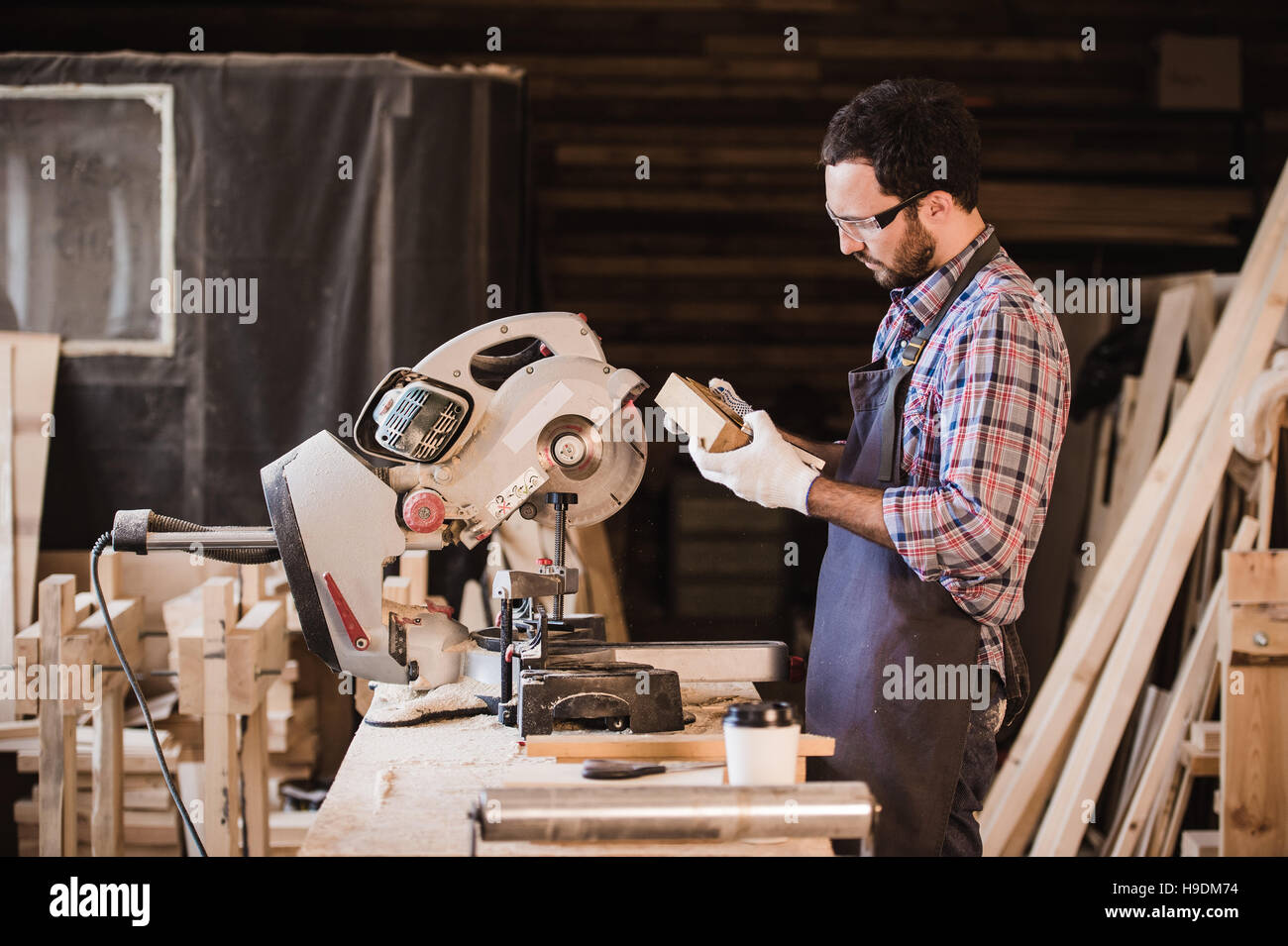 profession, carpentry, woodwork people concept - carpenter with wood plank and notebook checking his notes at workshop - Stock Image