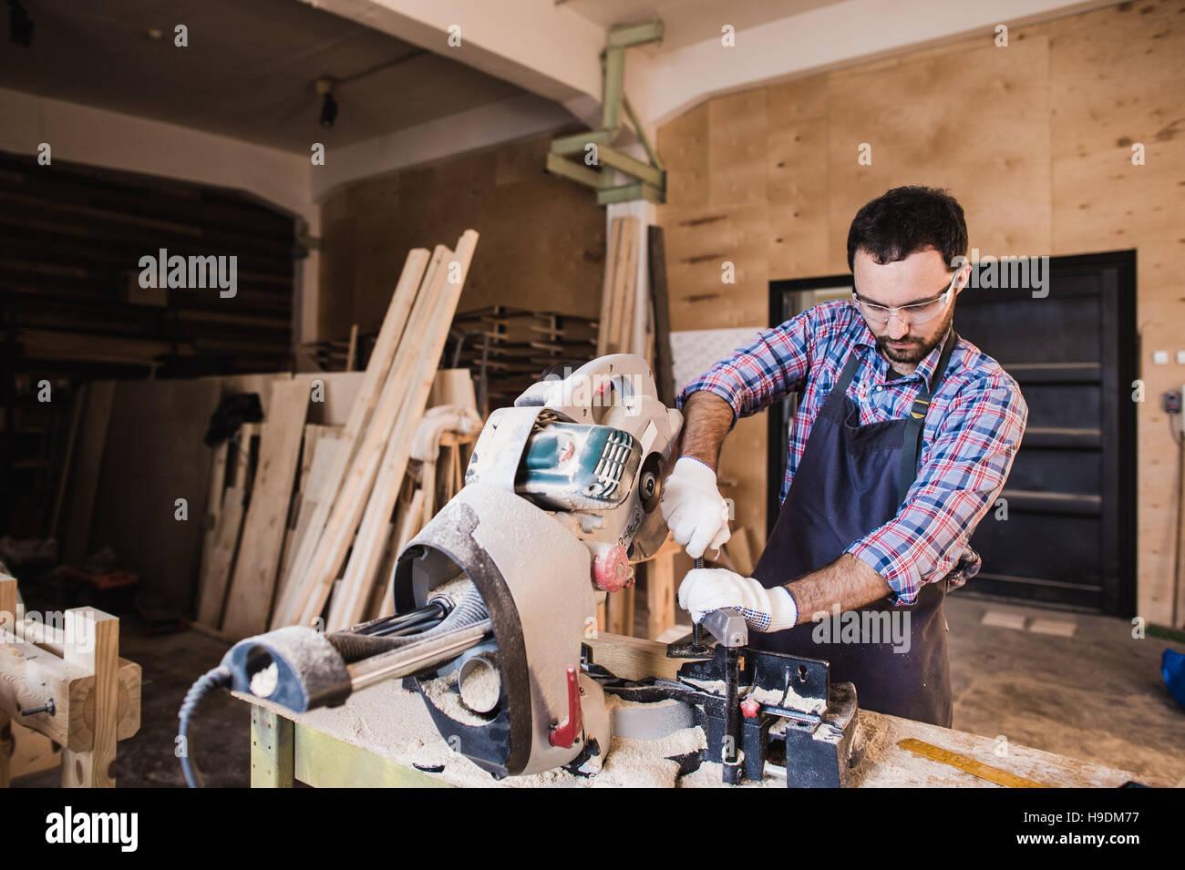 Carpenter Using Circular Saw for wood at his workshop - Stock Image