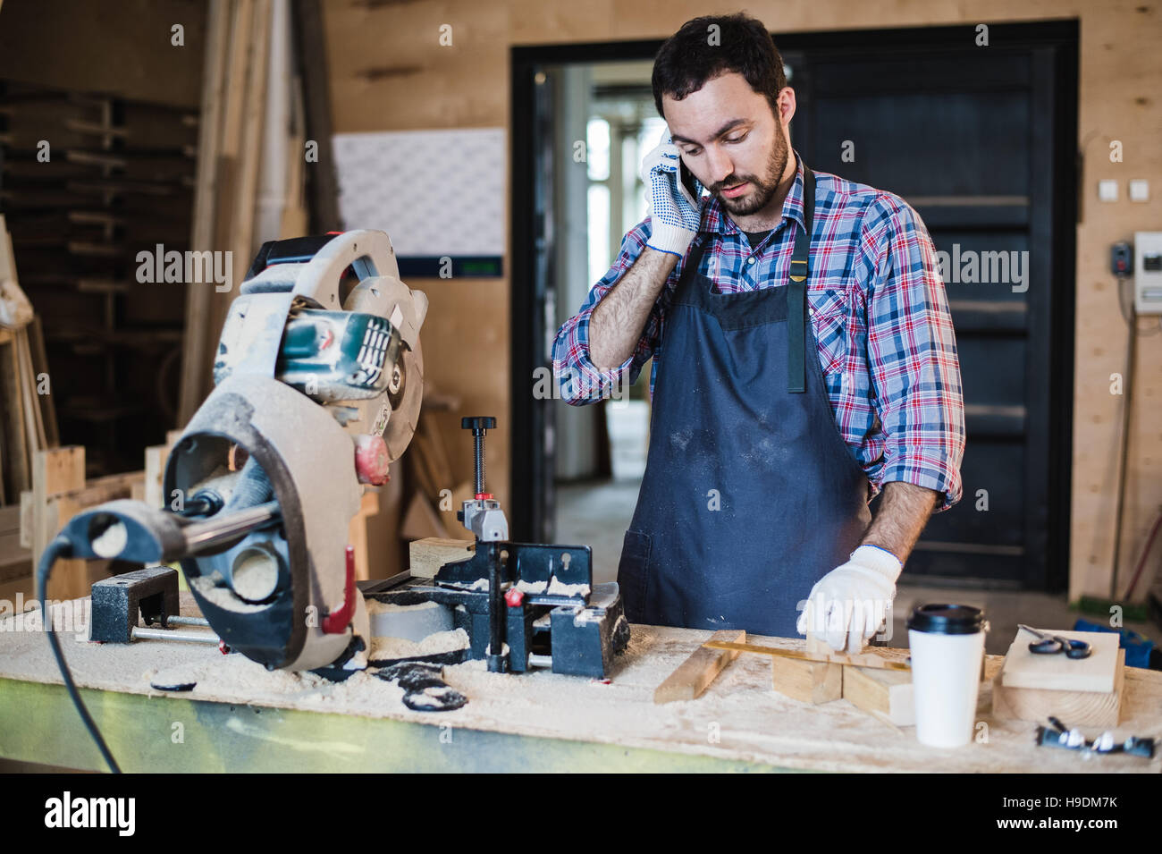 portrait of carpenter calling by smart phone at the workshop Stock Photo