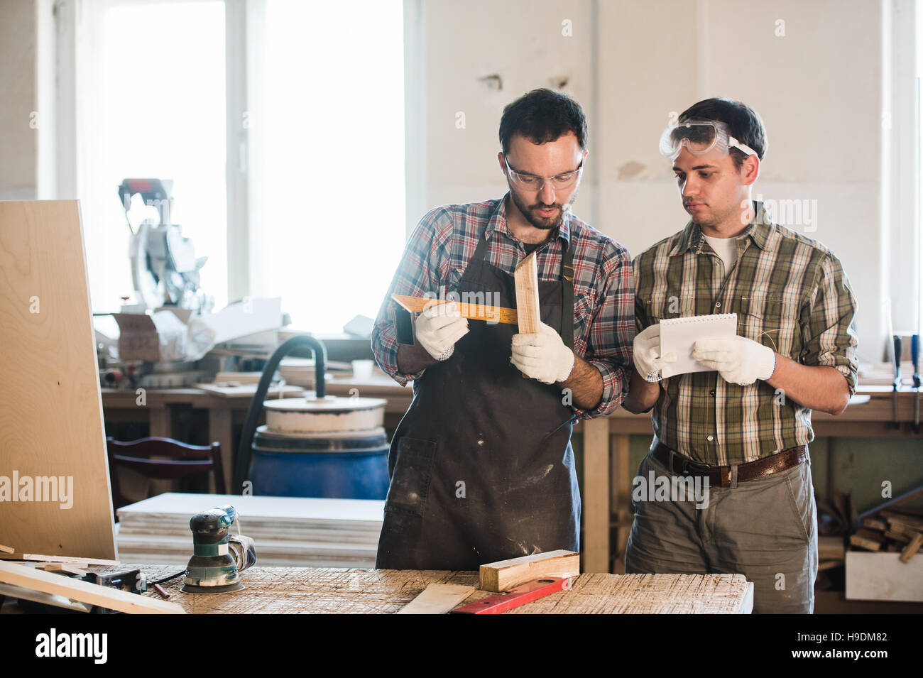 Happy male carpenter showing something to coworker at his notebook papers in workshop - Stock Image