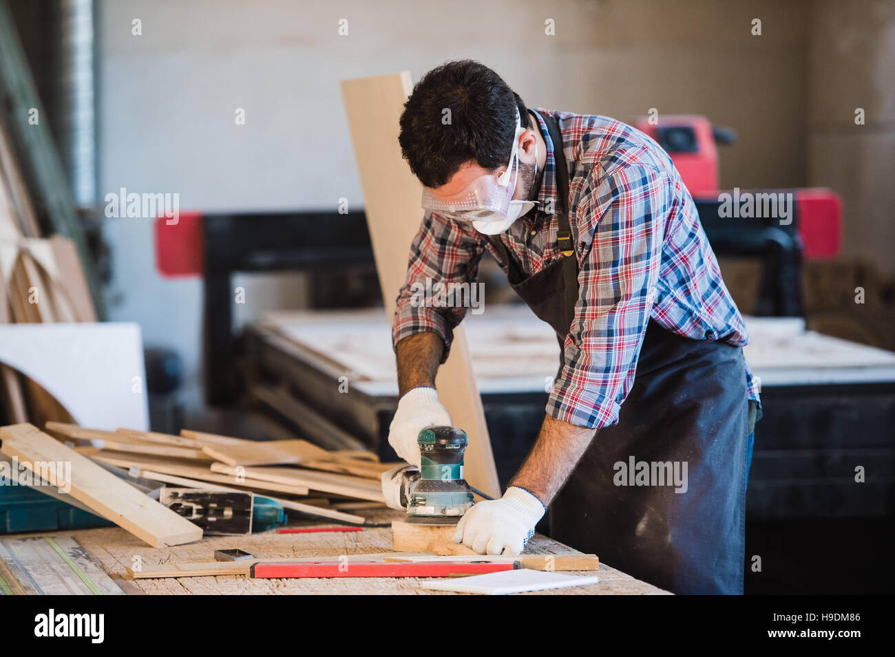 Worker grinds the wood of angular grinding machine - Stock Image