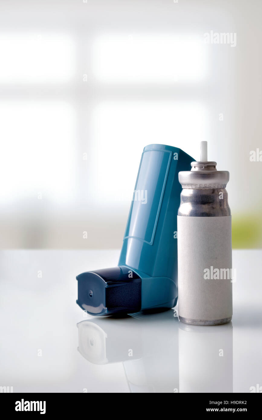 Cartridge and blue medicine inhaler on white glass table in a room. Front view. Vertical composition - Stock Image