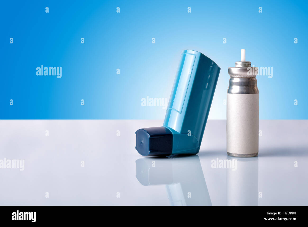 Cartridge and blue medicine inhaler on white glass table with blue gradient background. Front view. Horizontal composition - Stock Image
