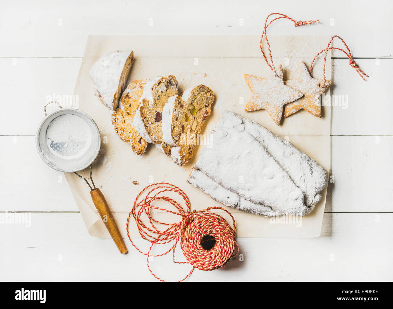 Traditional German Christmas cake Stollen cut in pieces, cookies, rope - Stock Image