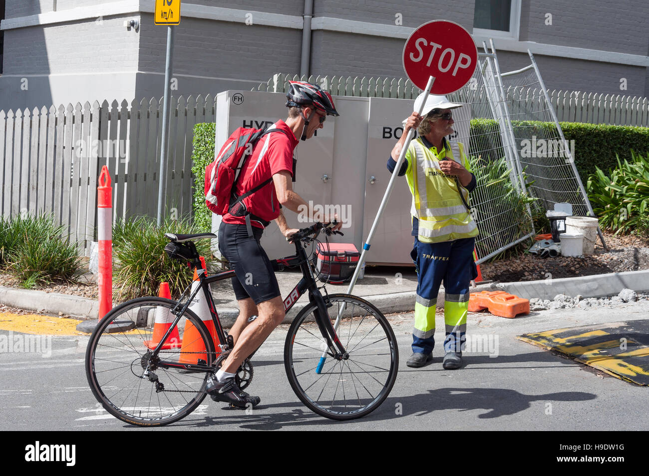 Cyclist waiting at roadworks stop sign, South Bank Parklands, Brisbane City, Brisbane, Queensland, Australia - Stock Image