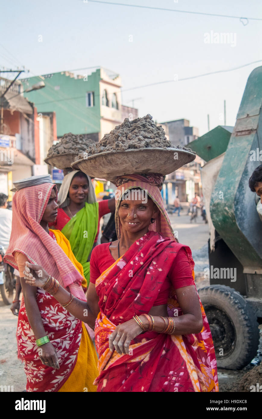 Women carrying cement on their head in Bhubaneswar, India. - Stock Image