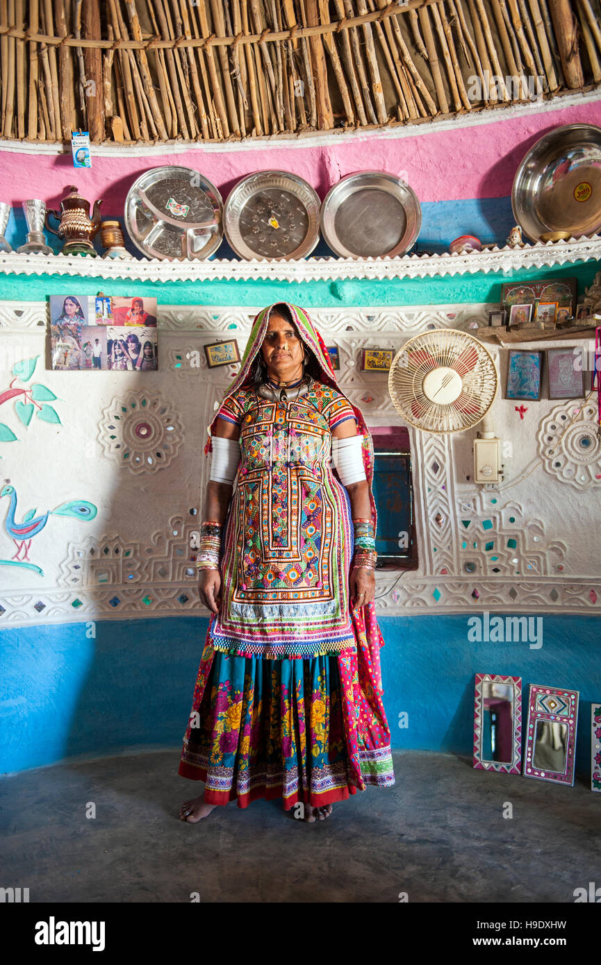 A Meghawal tribal woman standing inside of her family's ornately painted mud brick hut in Hodka, a semi-arid - Stock Image
