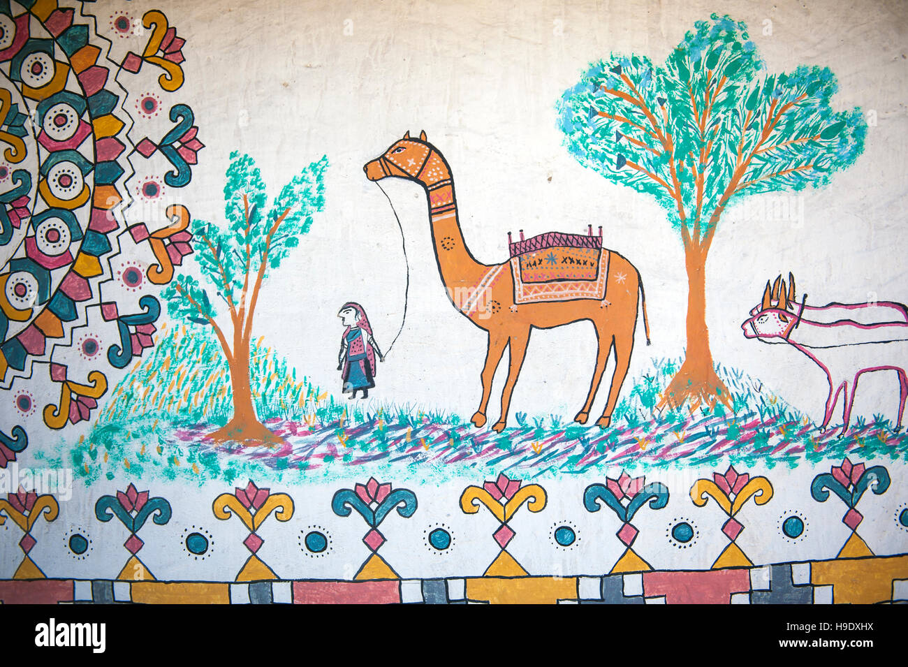 A painting of every day village life the inside wall of a Meghawal tribal house in Hodka, a semi-arid region bordering - Stock Image