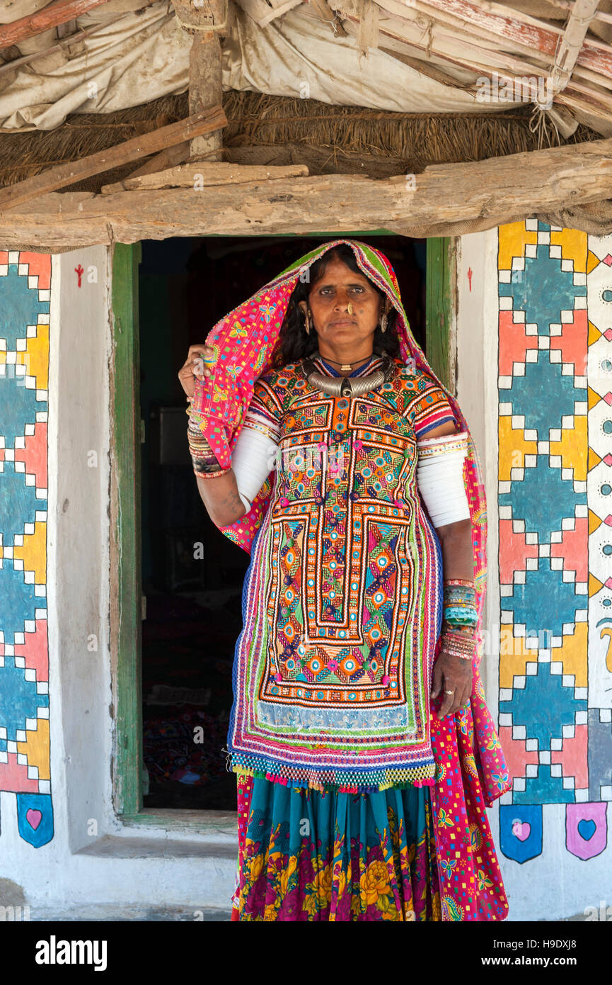 A Meghawal tribal woman standing in front of her family's ornately mud brick hut in Hodka, a semi-arid region - Stock Image
