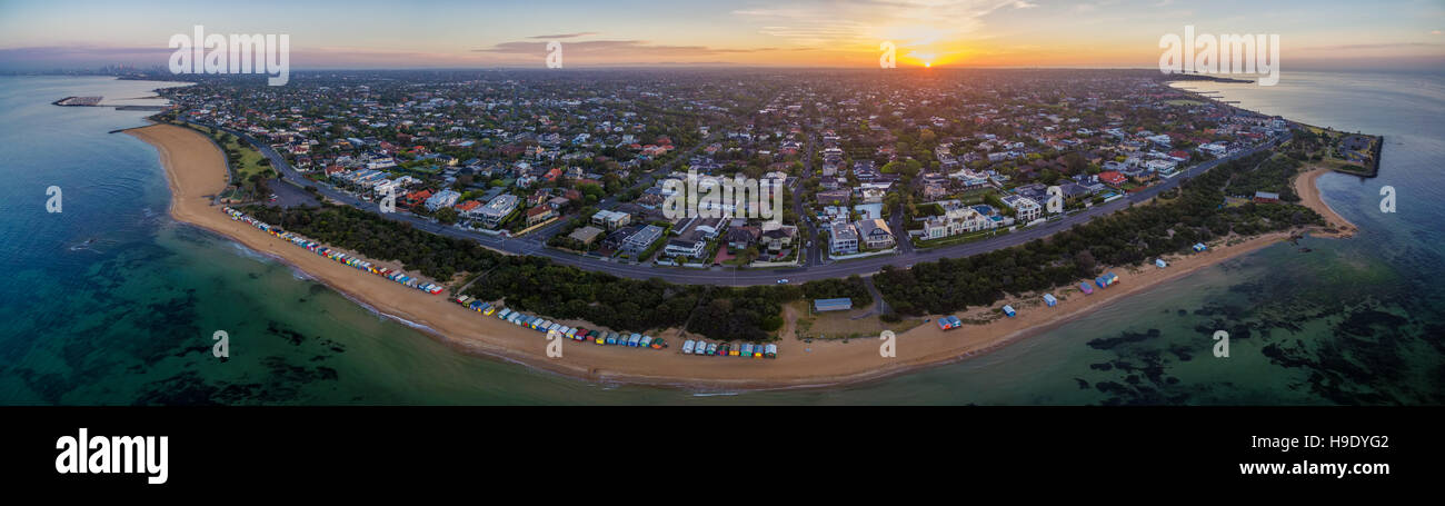 Aerial panorama of sunrise over Brighton suburb, showing iconic beach huts, houses, and the ocean. Melbourne, Victoria, Stock Photo