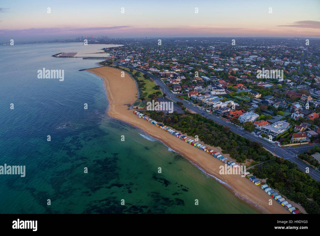 Aerial view of sunrise at Brighton Beach coastline with beach boxes, and CBD in the distance. Melbourne, Victoria, - Stock Image