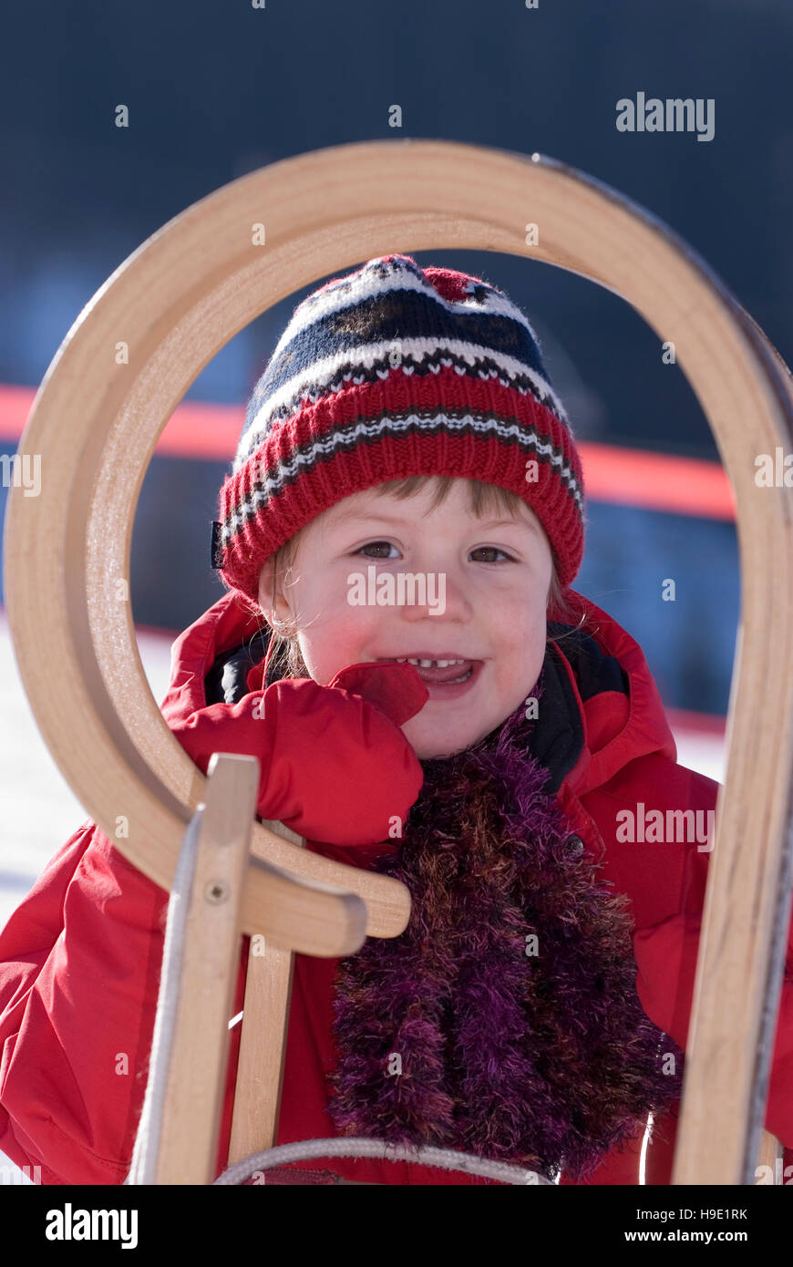 Child standing behind a sledge - Stock Image