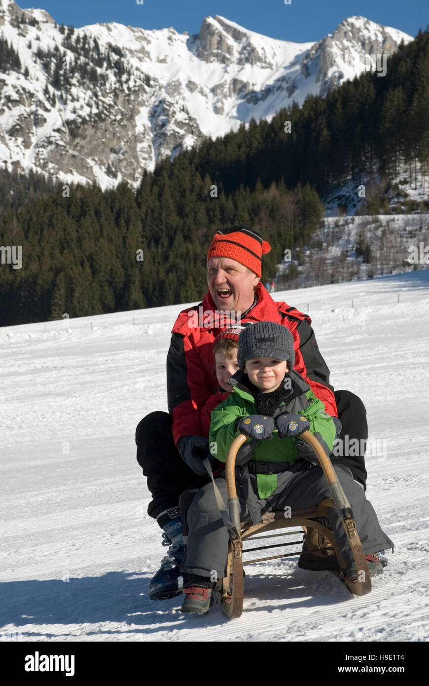 Man and children on a sledge - Stock Image