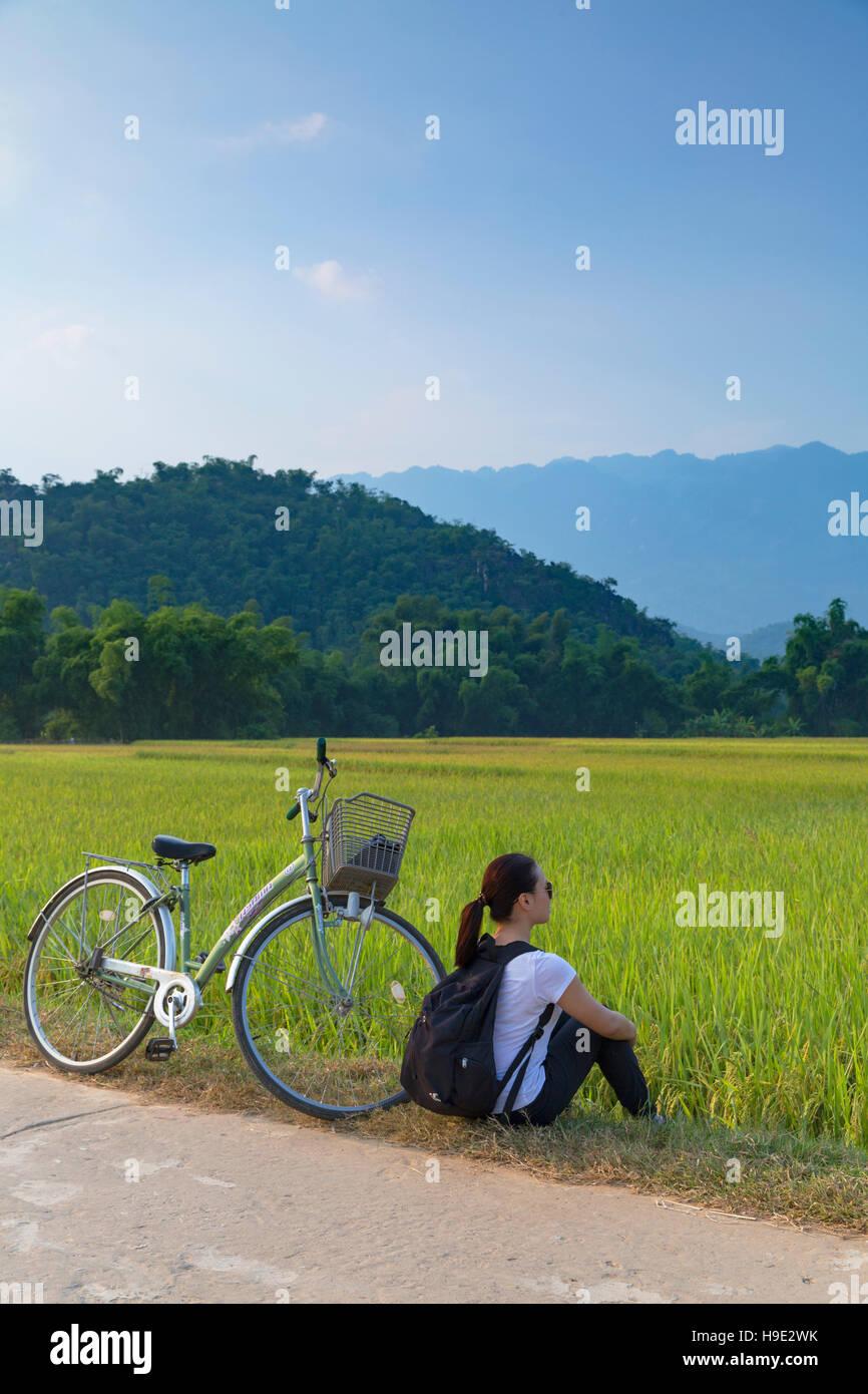Woman with bicycle in rice paddies, Mai Chau, Hoa Binh Province, Vietnam - Stock Image