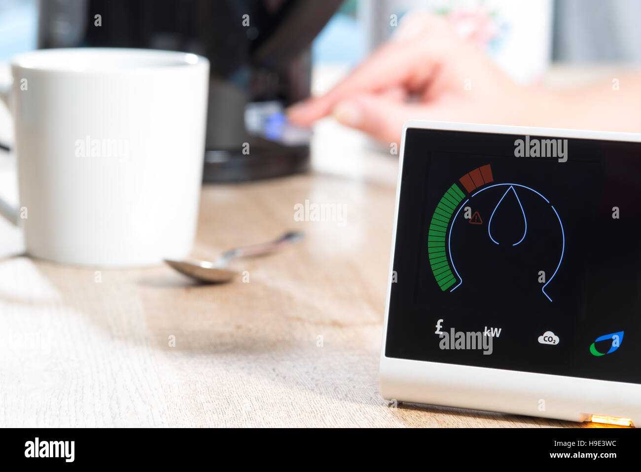 A smart meter is displayed on a  wooden surface near mug and spoon and a kettle which is being switched on by a - Stock Image