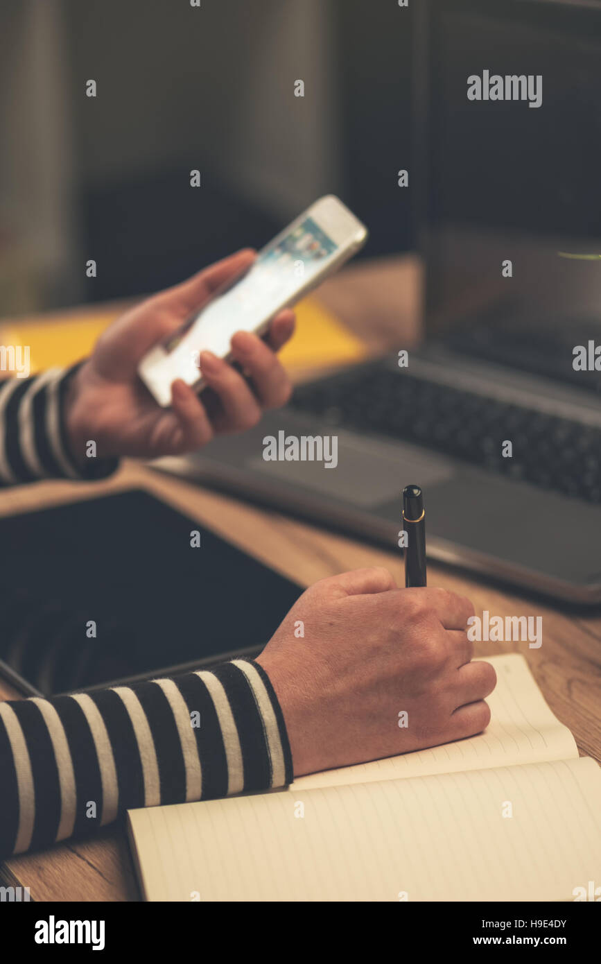 Businesswoman writing contacts names and phone numbers in notebook, low light office interior - Stock Image