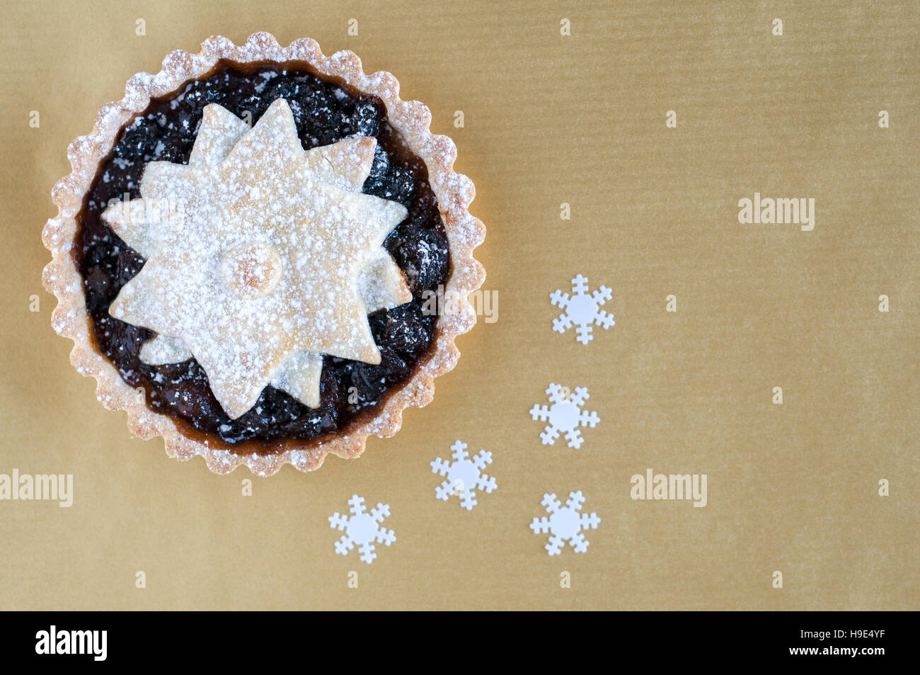 Christmas mincemeat pies, decorated with a star and dusted with icing sugar on a gold background - Stock Image