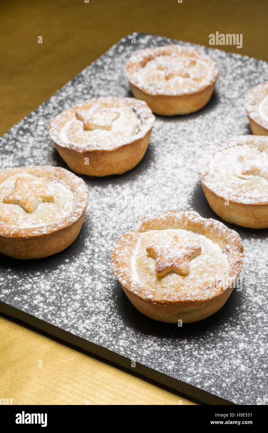 Christmas mincemeat pies, decorated with a star and dusted with icing sugar on slate and gold backgrounds - Stock Image