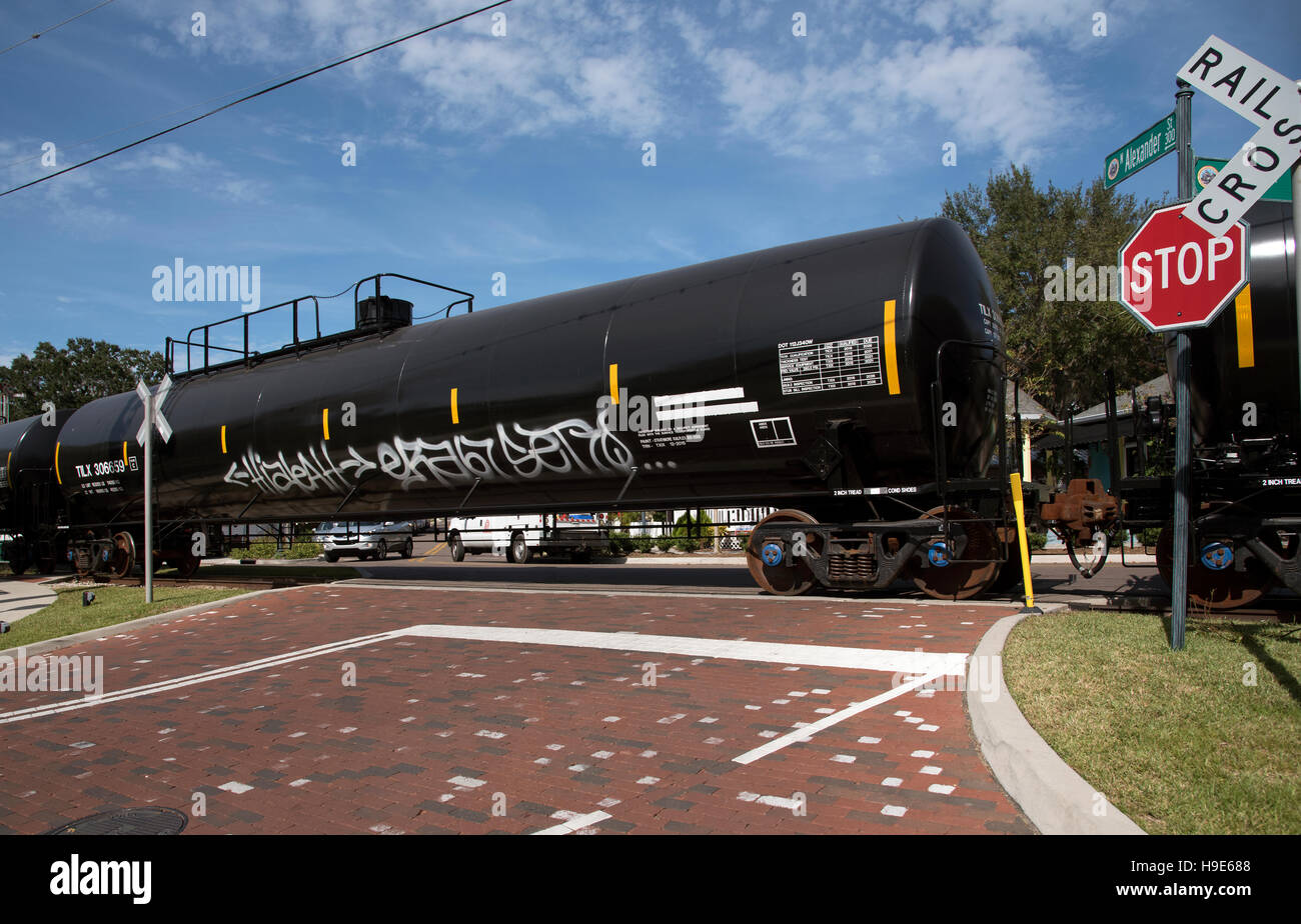 Mount Dora Florida USA -  Railroad freight train hauling liquid carrying trucks passing over unmanned crossing - Stock Image