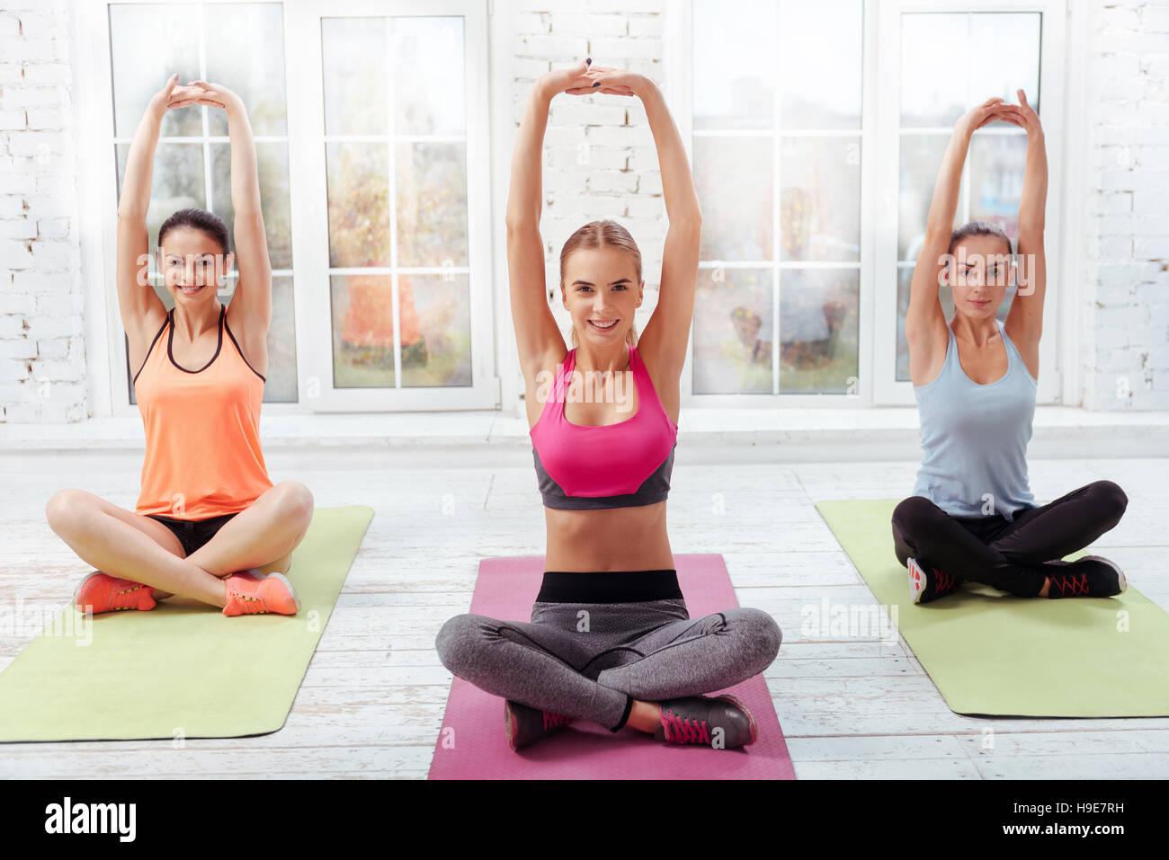Three pretty girls having yoga classes - Stock Image