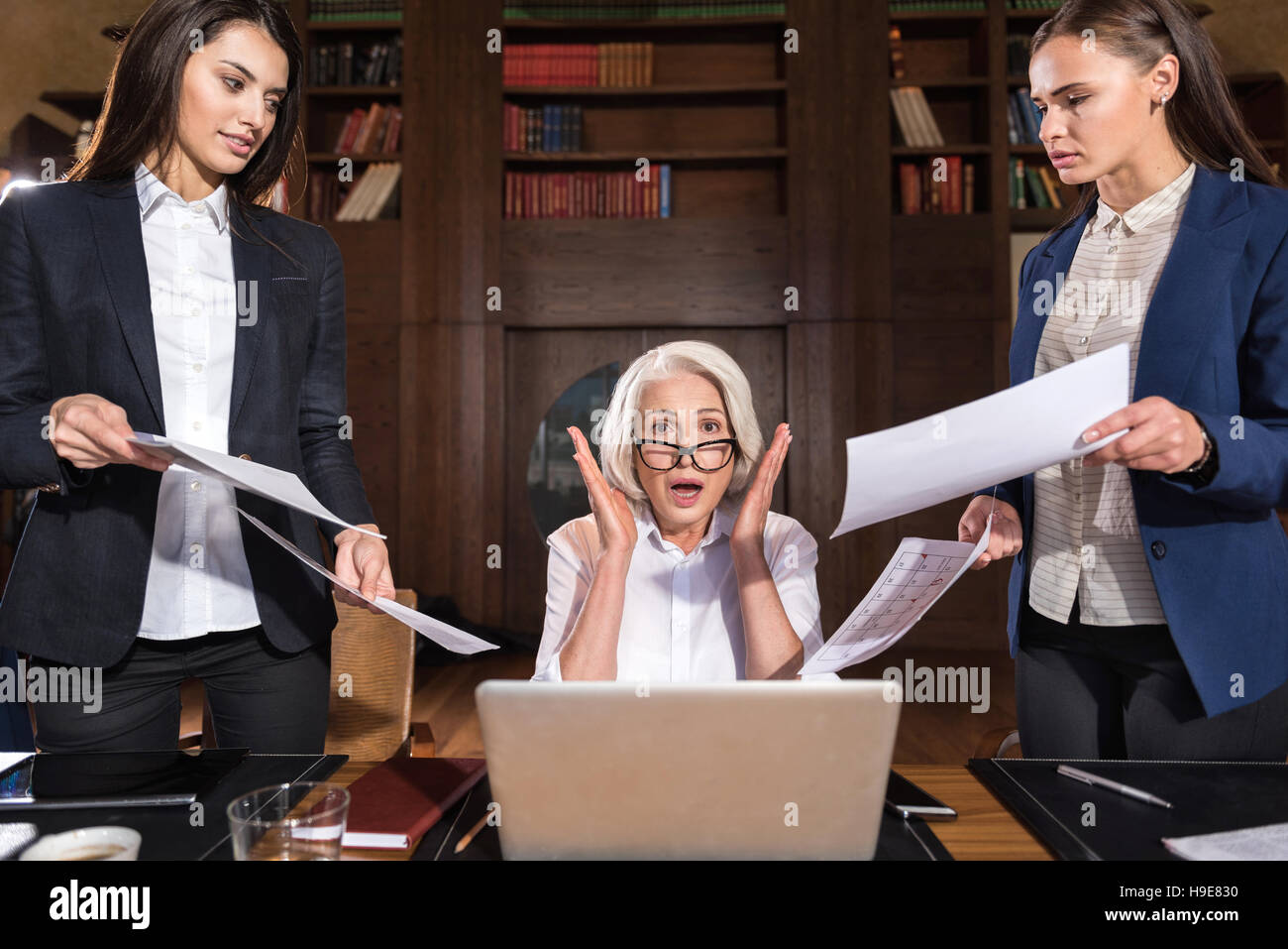 Exhausted boss and her female colleagues posing in an office - Stock Image